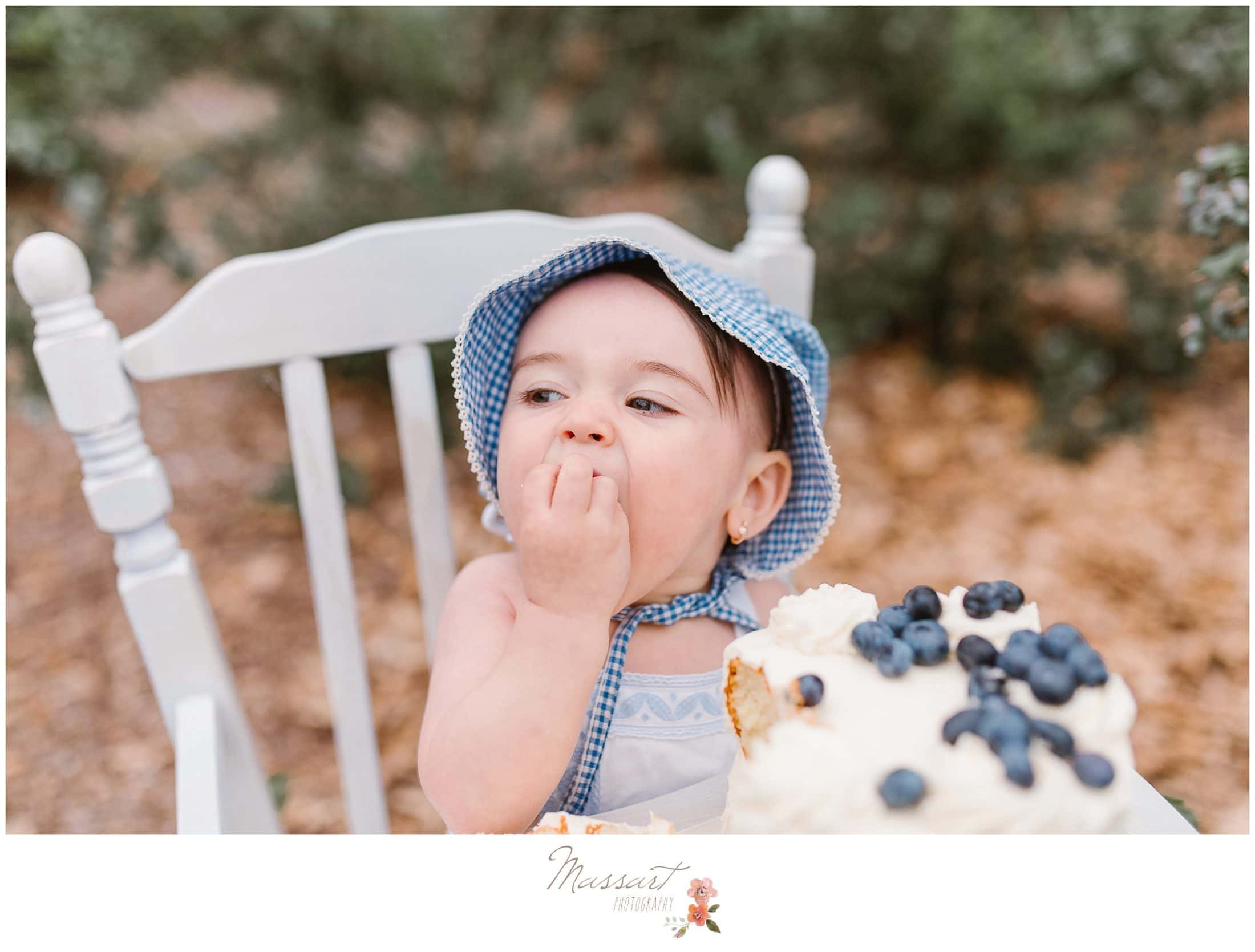 baby girl messily eats her blueberry cake during her cake smash session photographed by Massart Photography Rhode Island