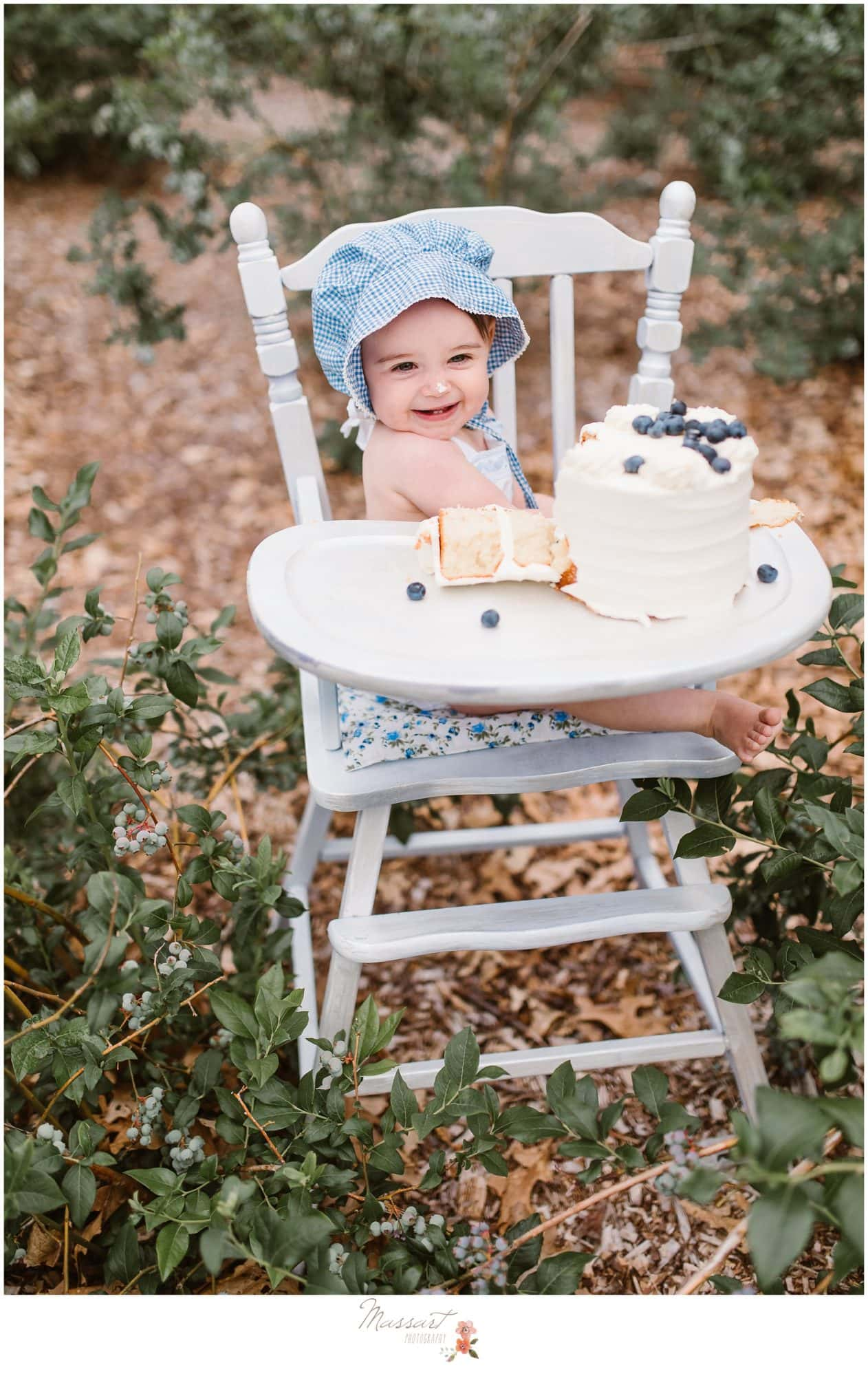Silly one year old poses while smashing her blueberry cake during her milestone session photographed by Massart Photography RI