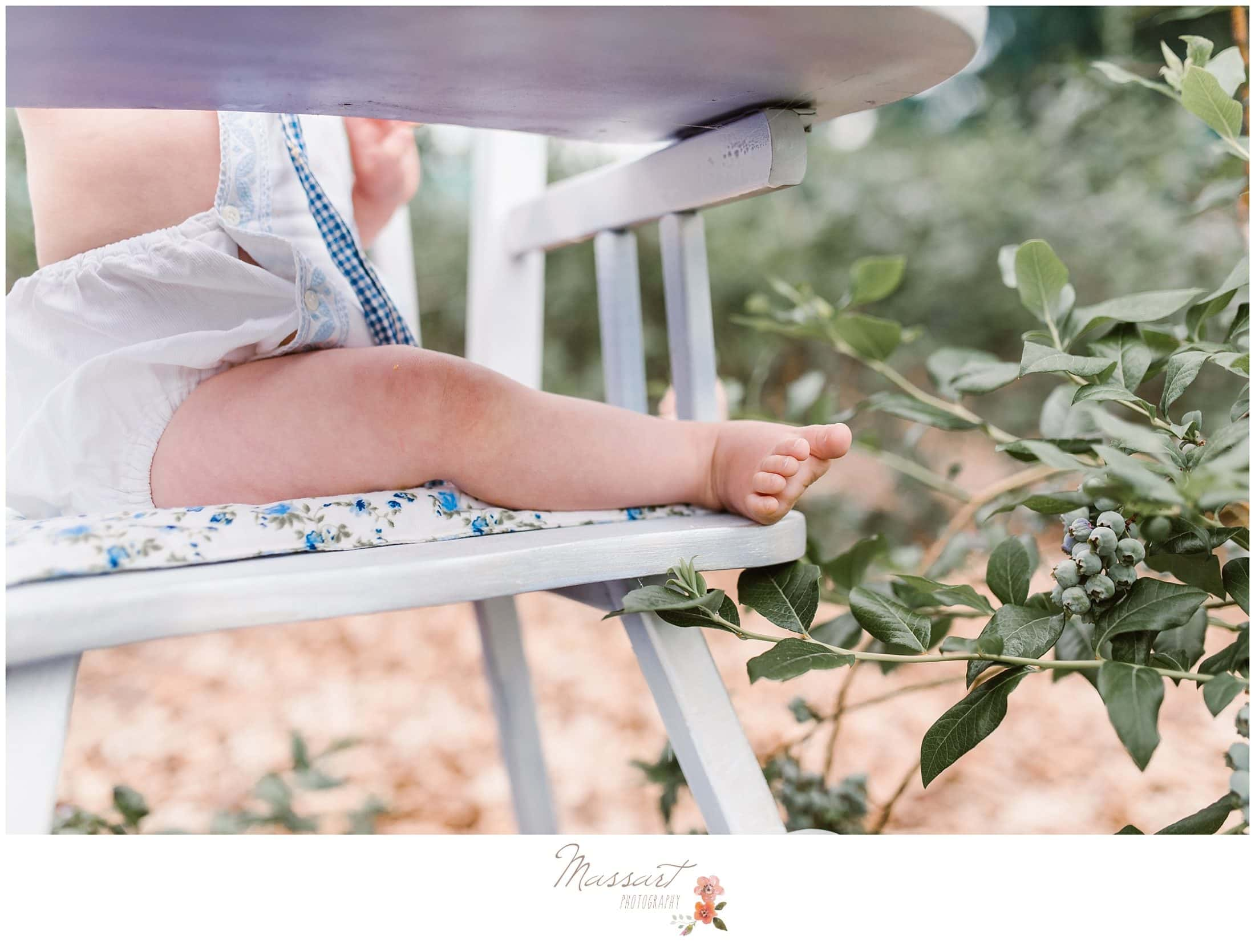 Detail portrait of baby legs while she sits in the high chair at the blueberry farm during cake smash session photographed by Massart Photography RI