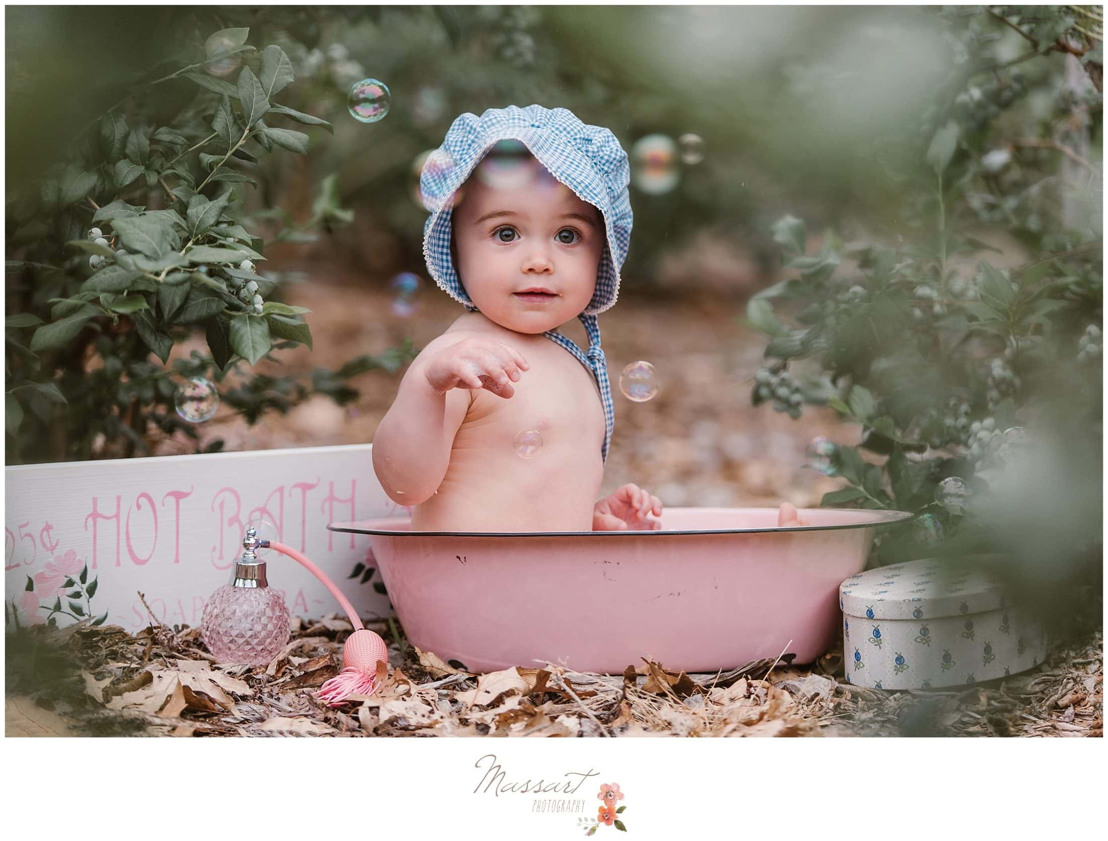 Baby girl sits in rustic bath during her milestone portrait session photographed by Massart Photography Rhode Island