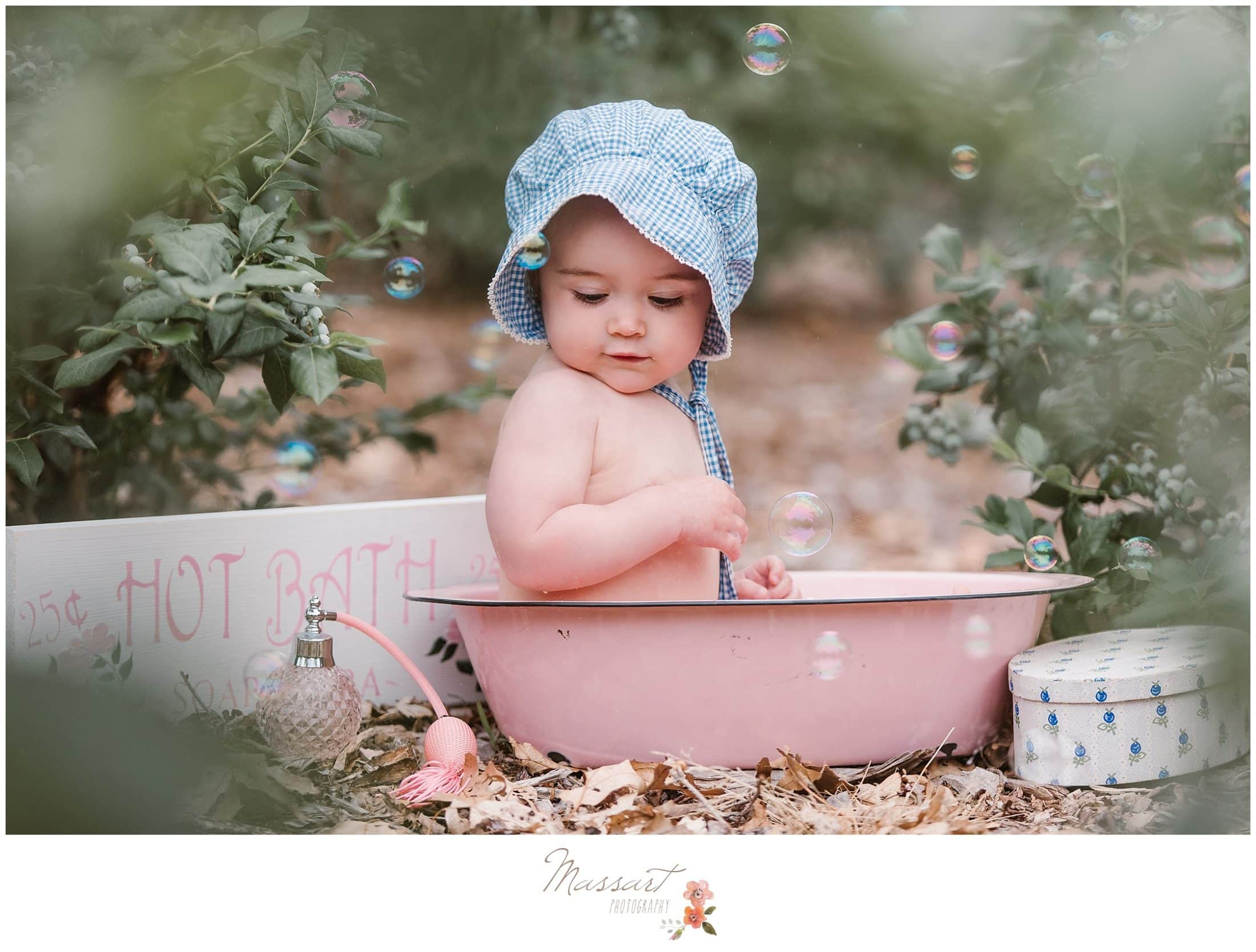 Baby girl sits in rustic bath surrounded by bubbles during her milestone portrait session photographed by Massart Photography of Rhode Island