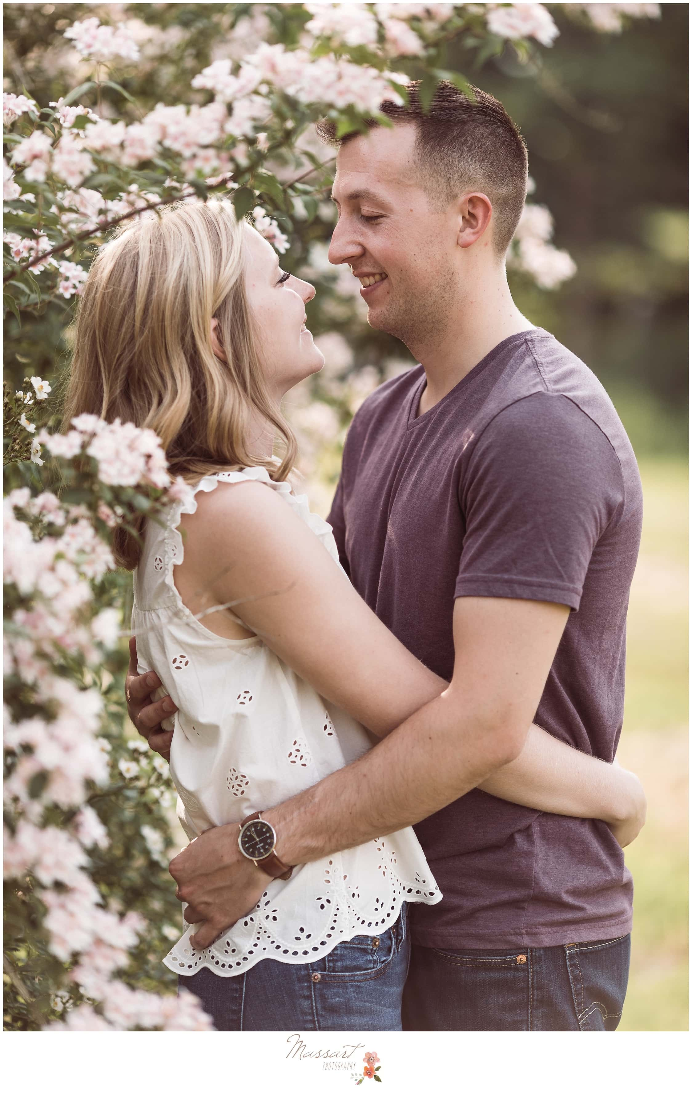 Couple stands near beautiful pink flowers during their engagement session photographed by Massart Photography of Warwick, RI