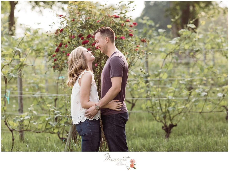 Newly engaged couple stand together outdoors during their engagement portrait session photographed by Massart Photography RI