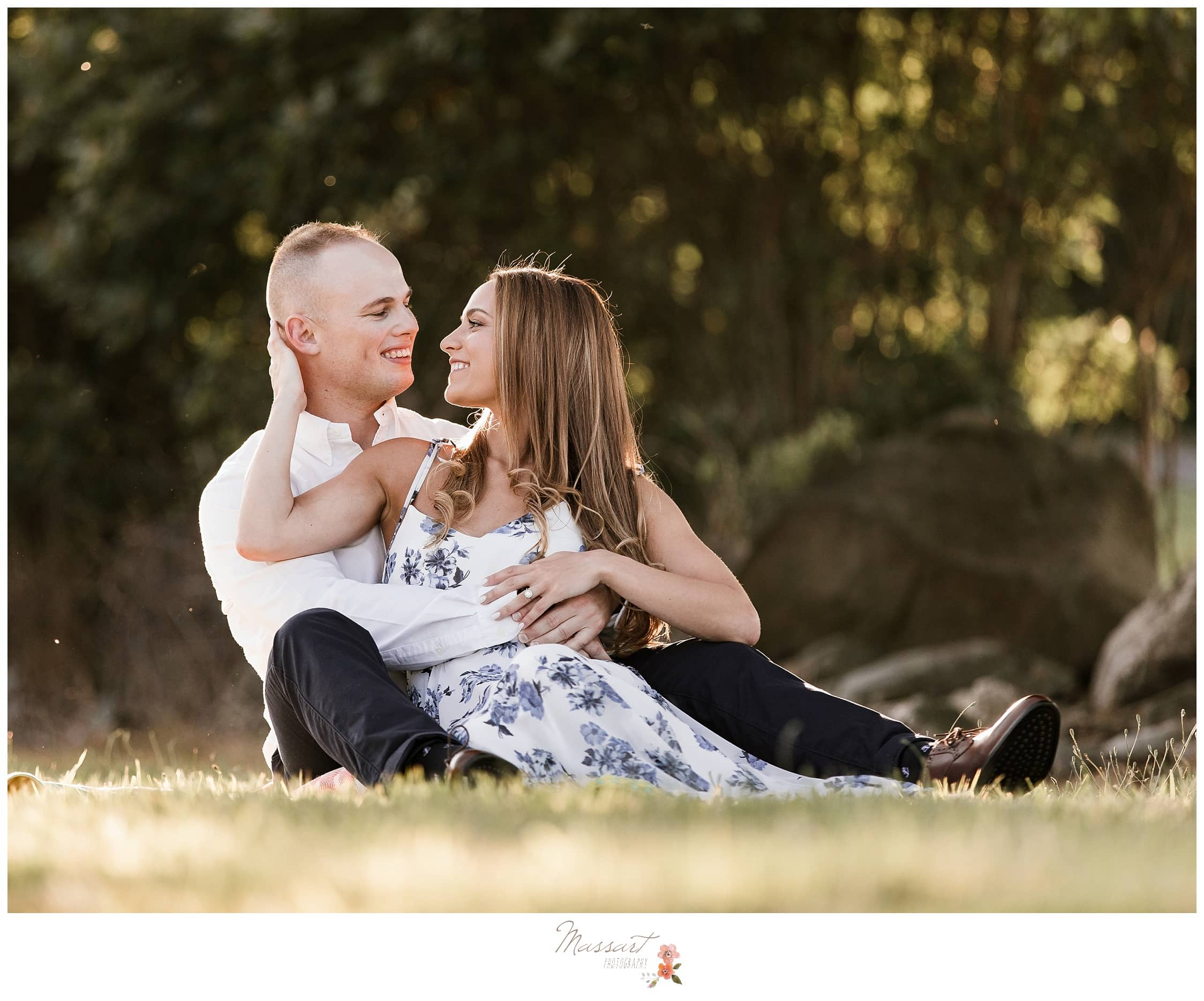 Newly engaged couple sits outside in the grass together during their engagement portrait session photographed by Massart Photography Rhode Island