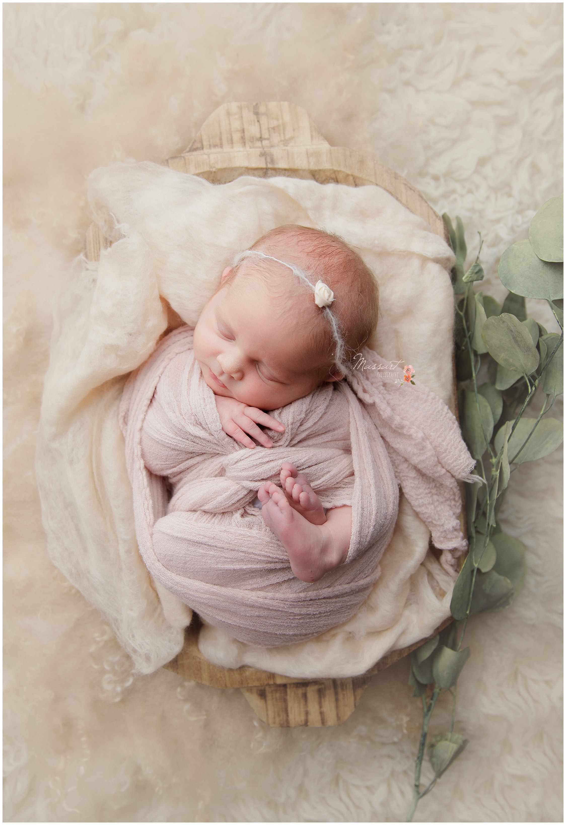 Newborn baby girl lays in white basket with pink blankets during her newborn portrait session photographed by Massart Photography Rhode Island