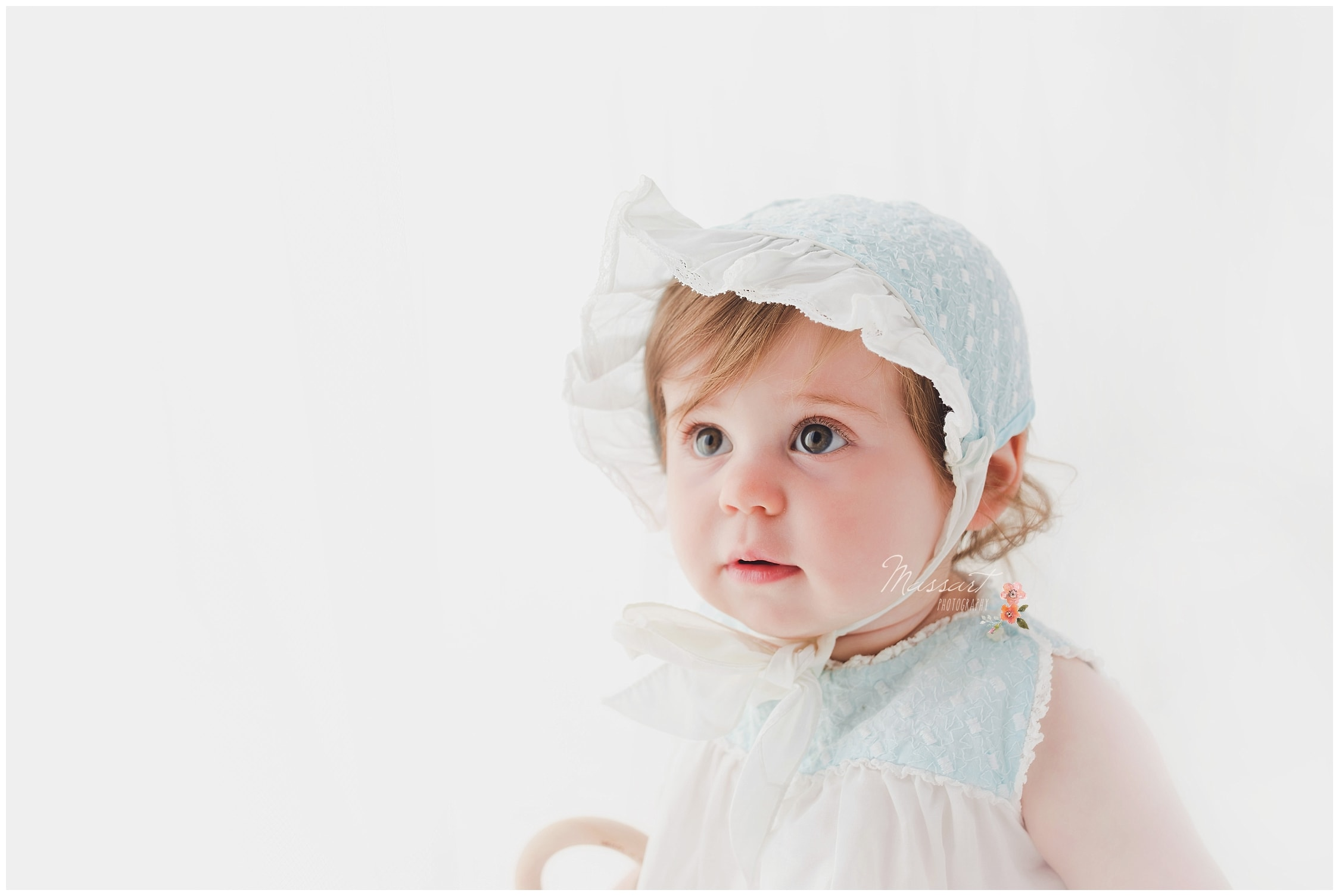 Baby girl in a white bonnet during her milestone portrait session photographed by Massart Photography RI