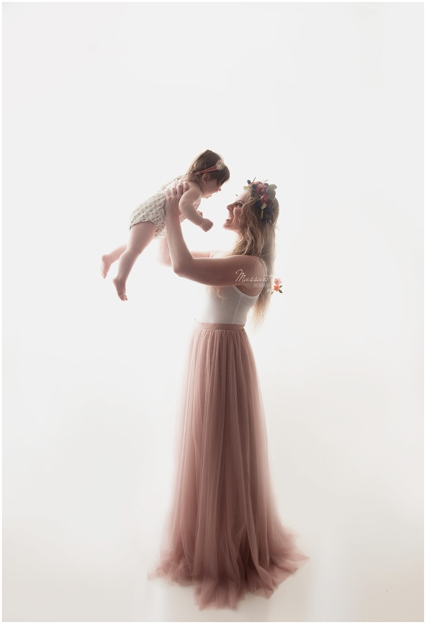 Mom holds baby girl wearing a pink tulle skirt photographed by Massart Photography RI