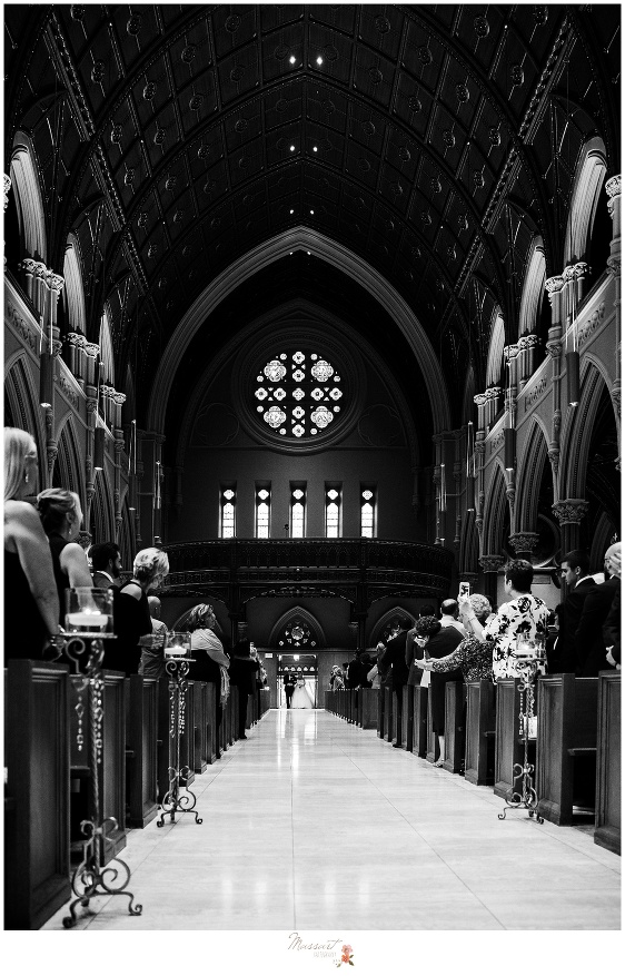 Black and white portrait of the cathedral as the bride and her father walk down the aisle photographed by Massart Photography RI