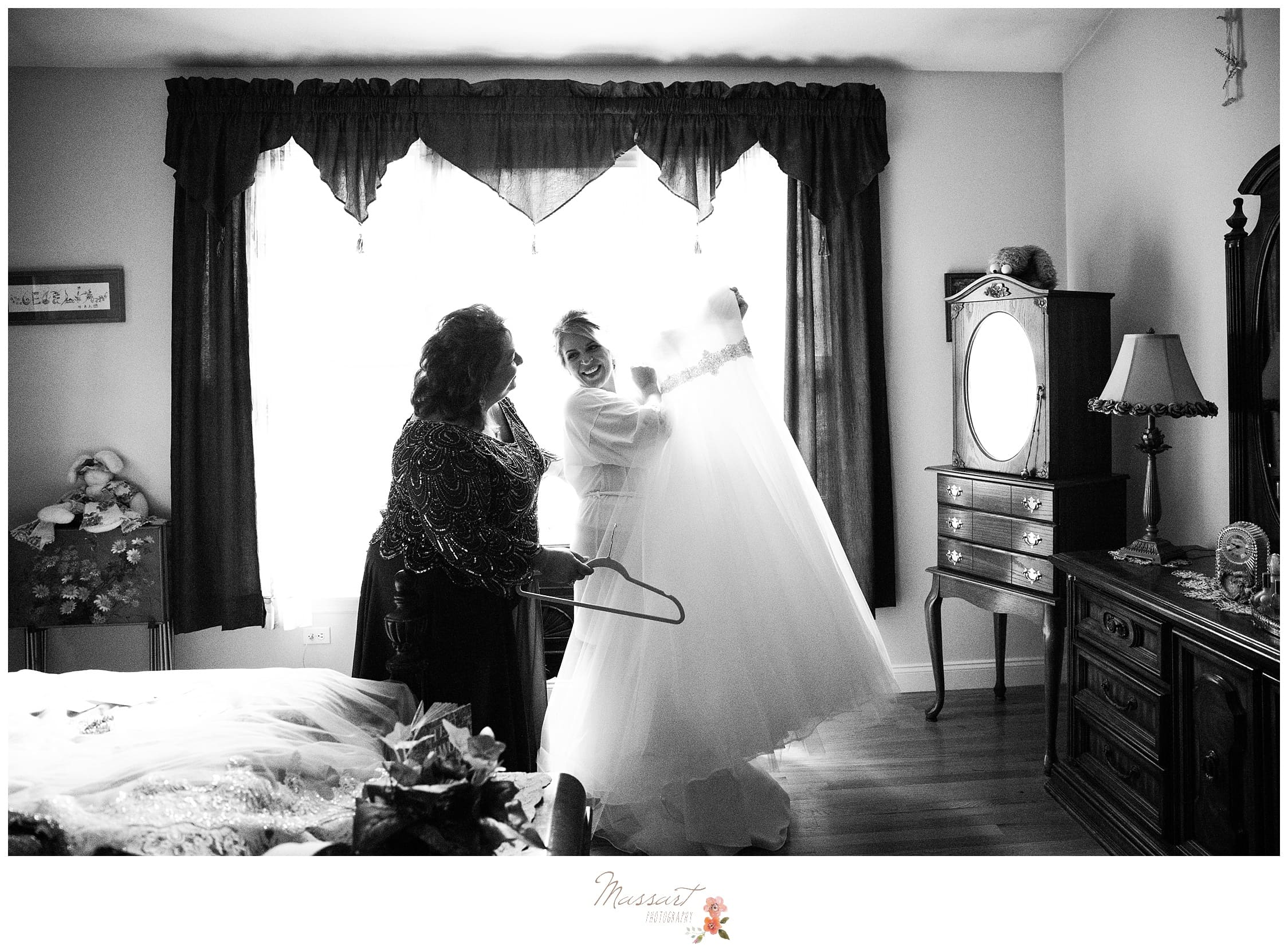 Bride takes her wedding gown off the hanger just before putting it on photographed by Massart Photography Rhode Island