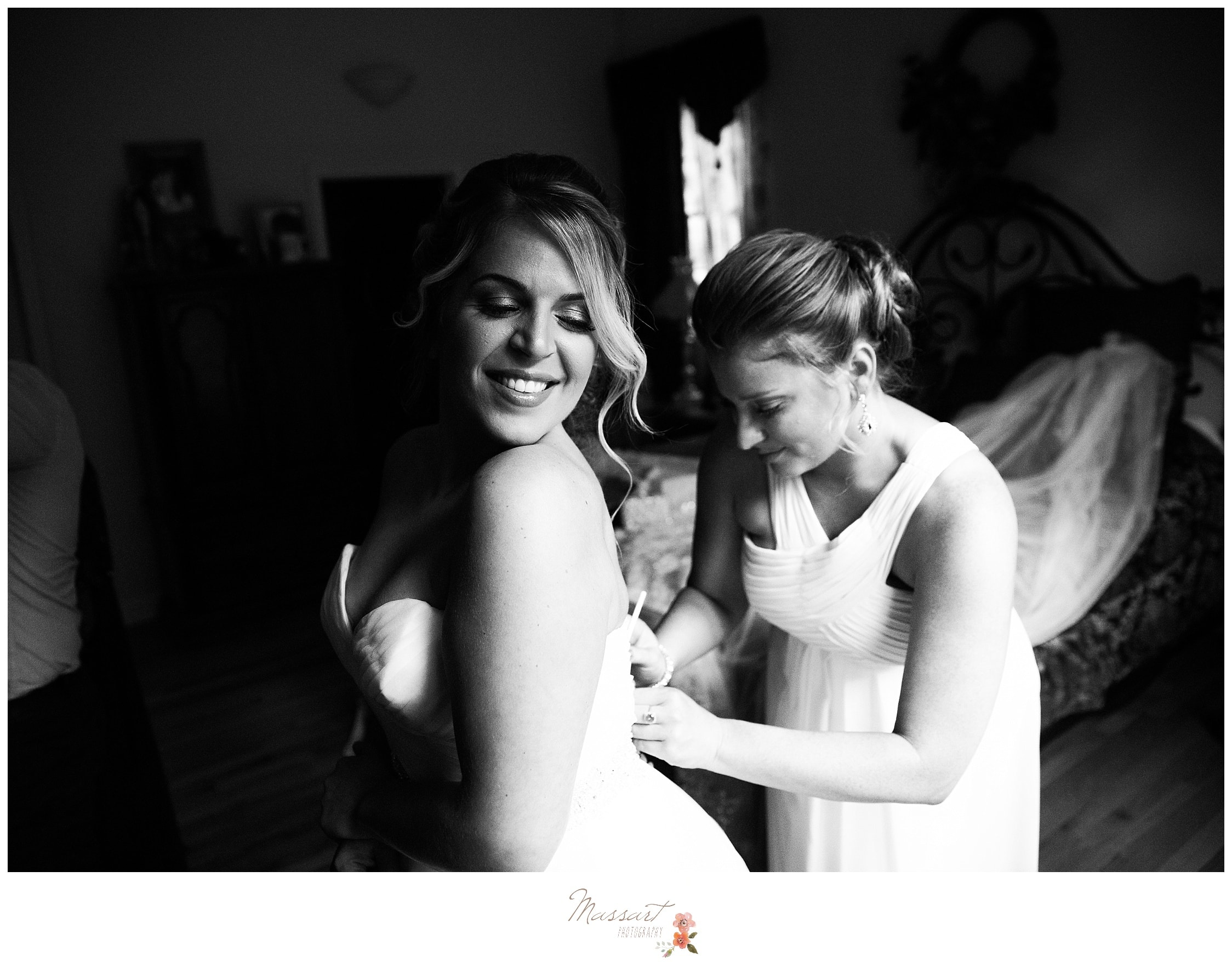 Black and white portrait of the bride putting on the wedding gown before the ceremony photographed by Massart Photography RI