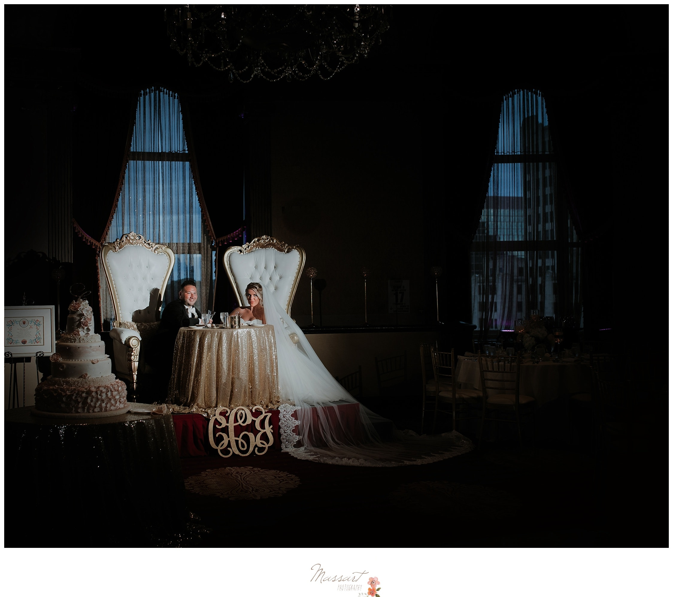 The bride and groom sit at their vintage chairs at the wedding reception photographed by Massart Photography Rhode Island