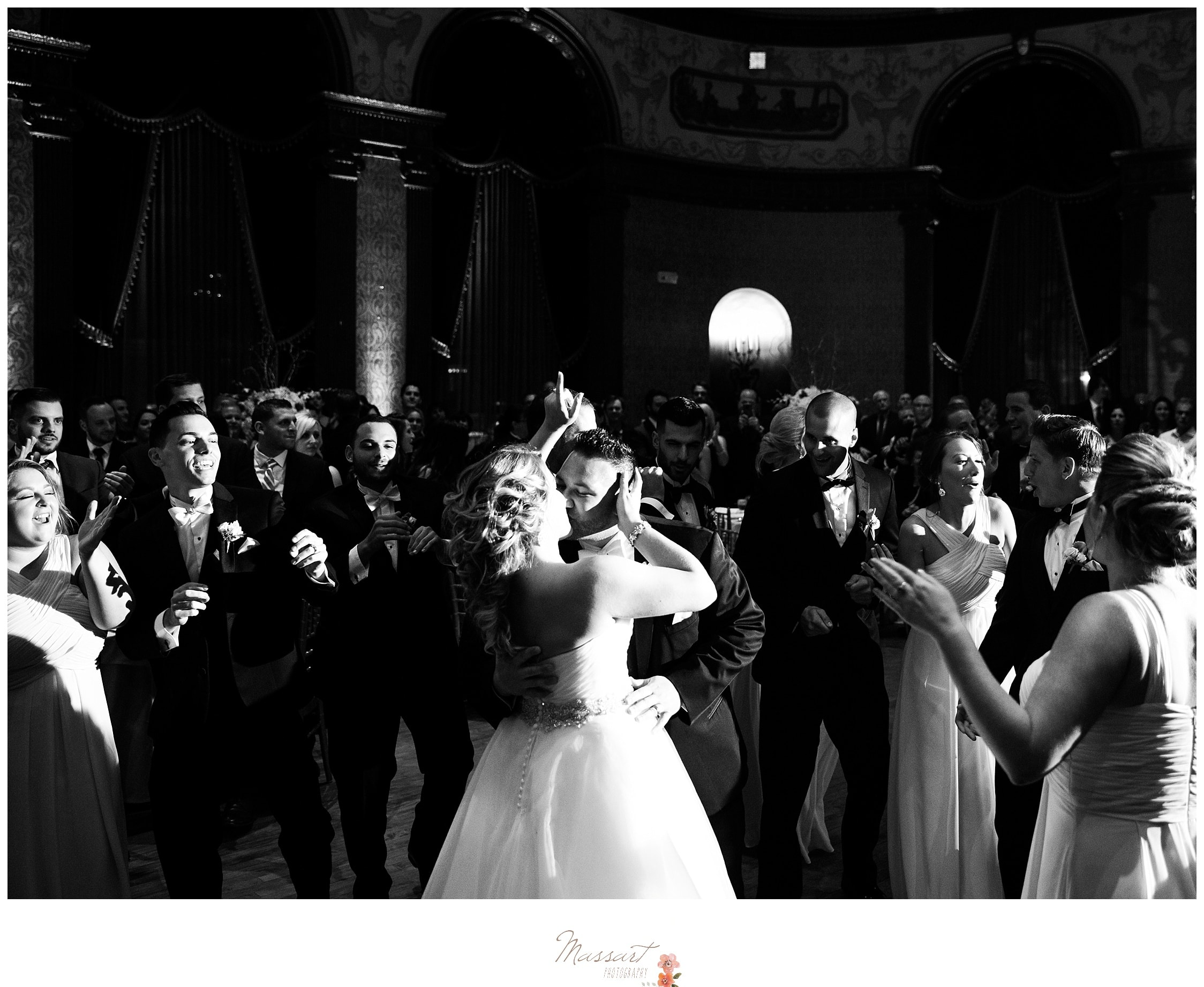 The bride and groom kiss on the dance floor surrounded by their friends and family photographed by Massart Photography Rhode Island