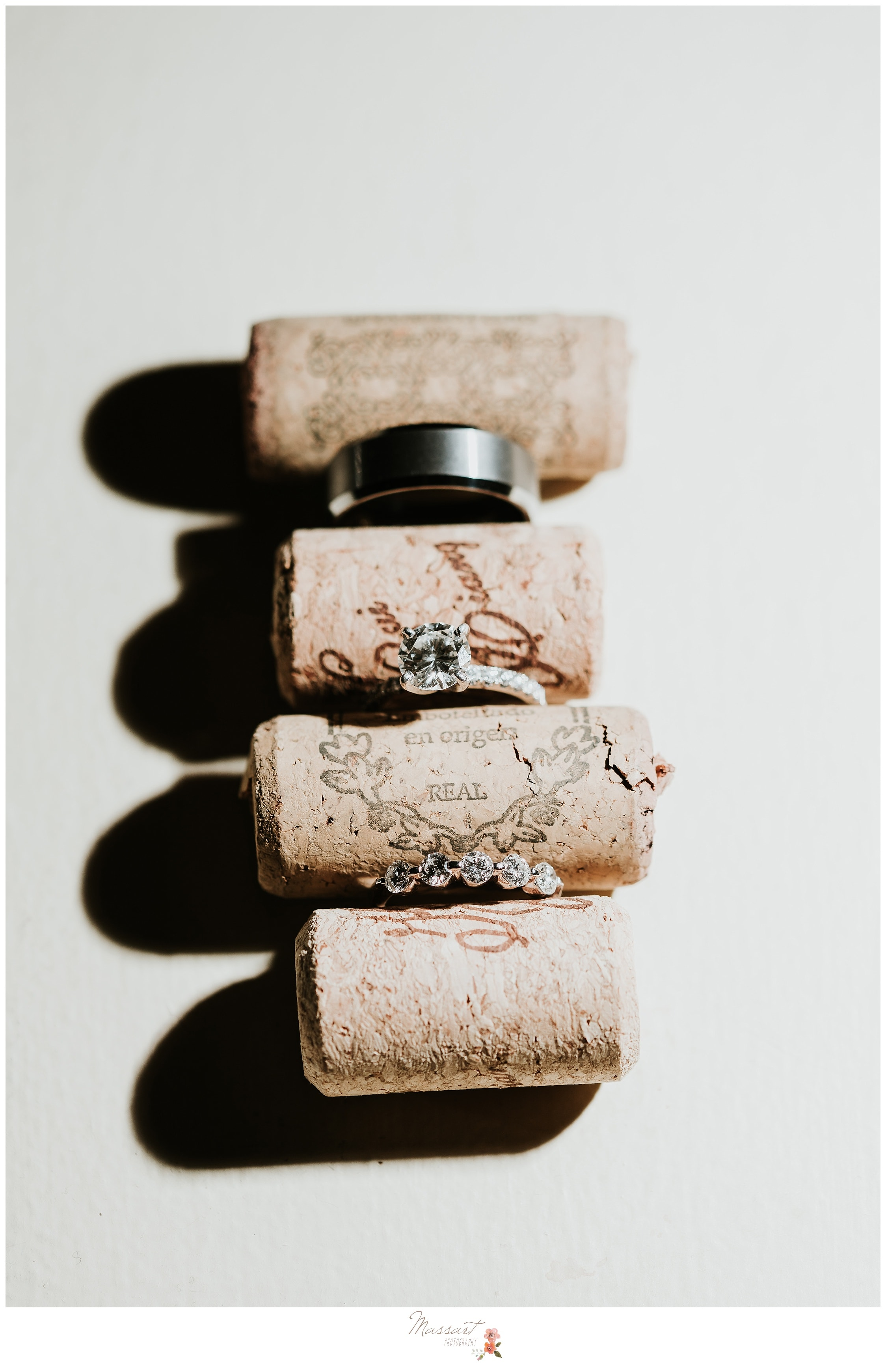 Bride and groom's wedding rings amongst wine corks from the Biltmore wedding reception Photographed by Massart Photography RI