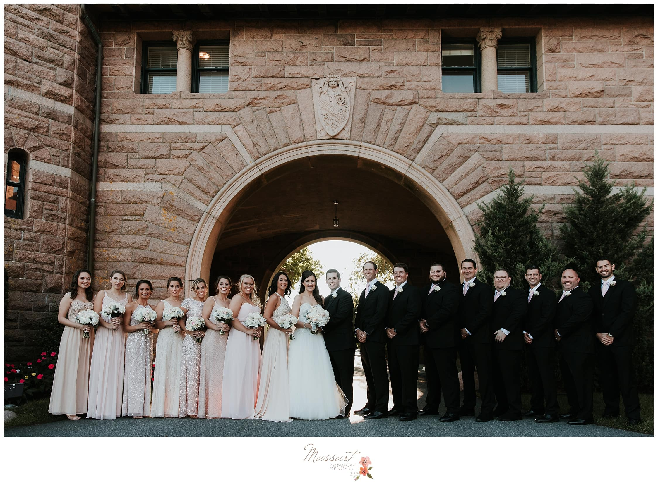 Wedding party takes formal portraits under the arch at Ocean Cliff photographed by Massart Photography RI