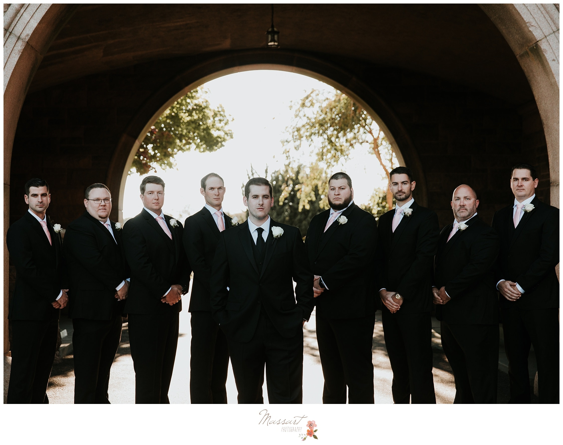 Groom and groomsmen under the arch at Ocean Cliff photographed by Massart Photography RI
