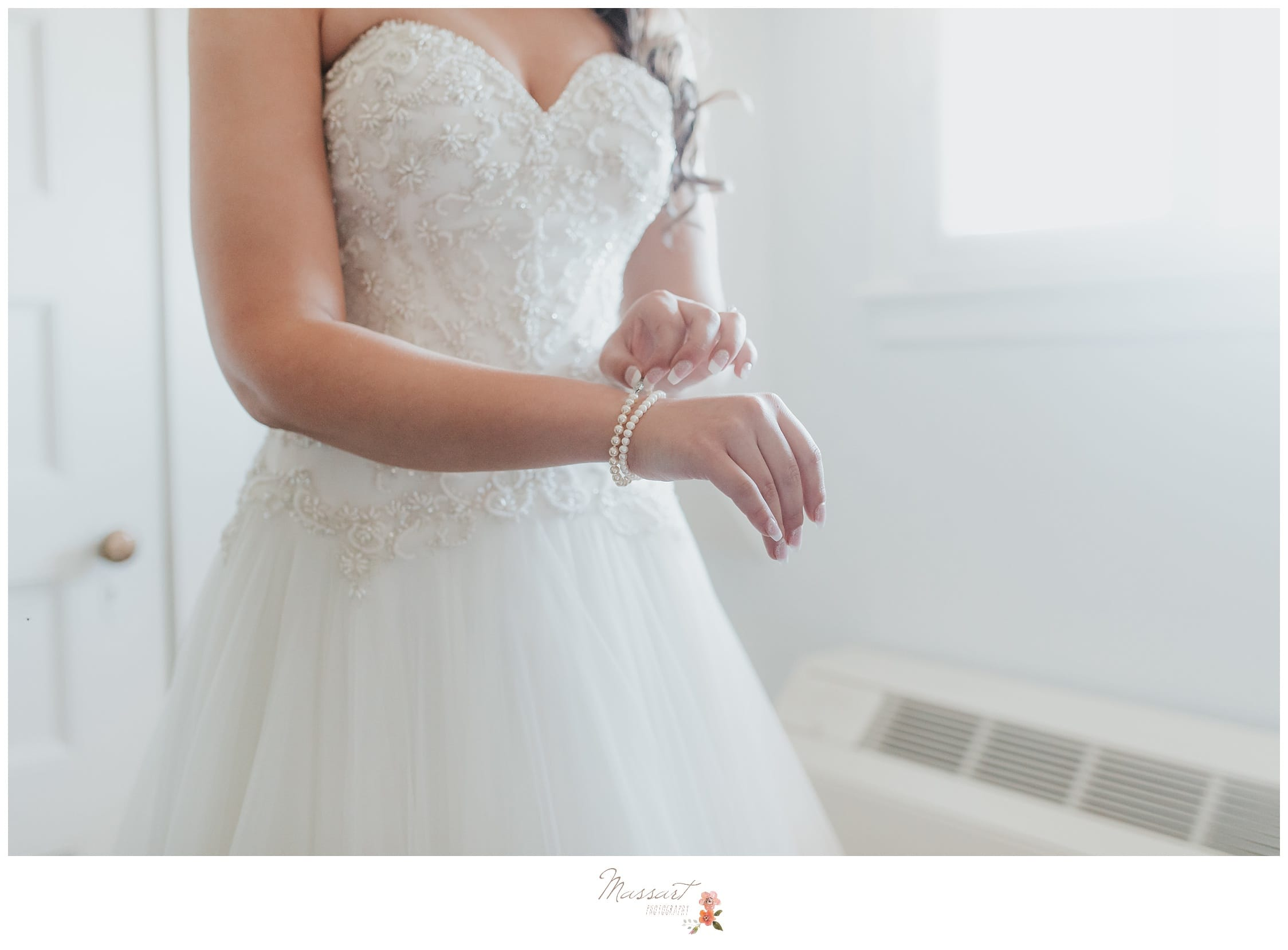 Bride puts on the finishing touches of getting ready and puts on her jewelry photographed by Massart Photography Rhode Island