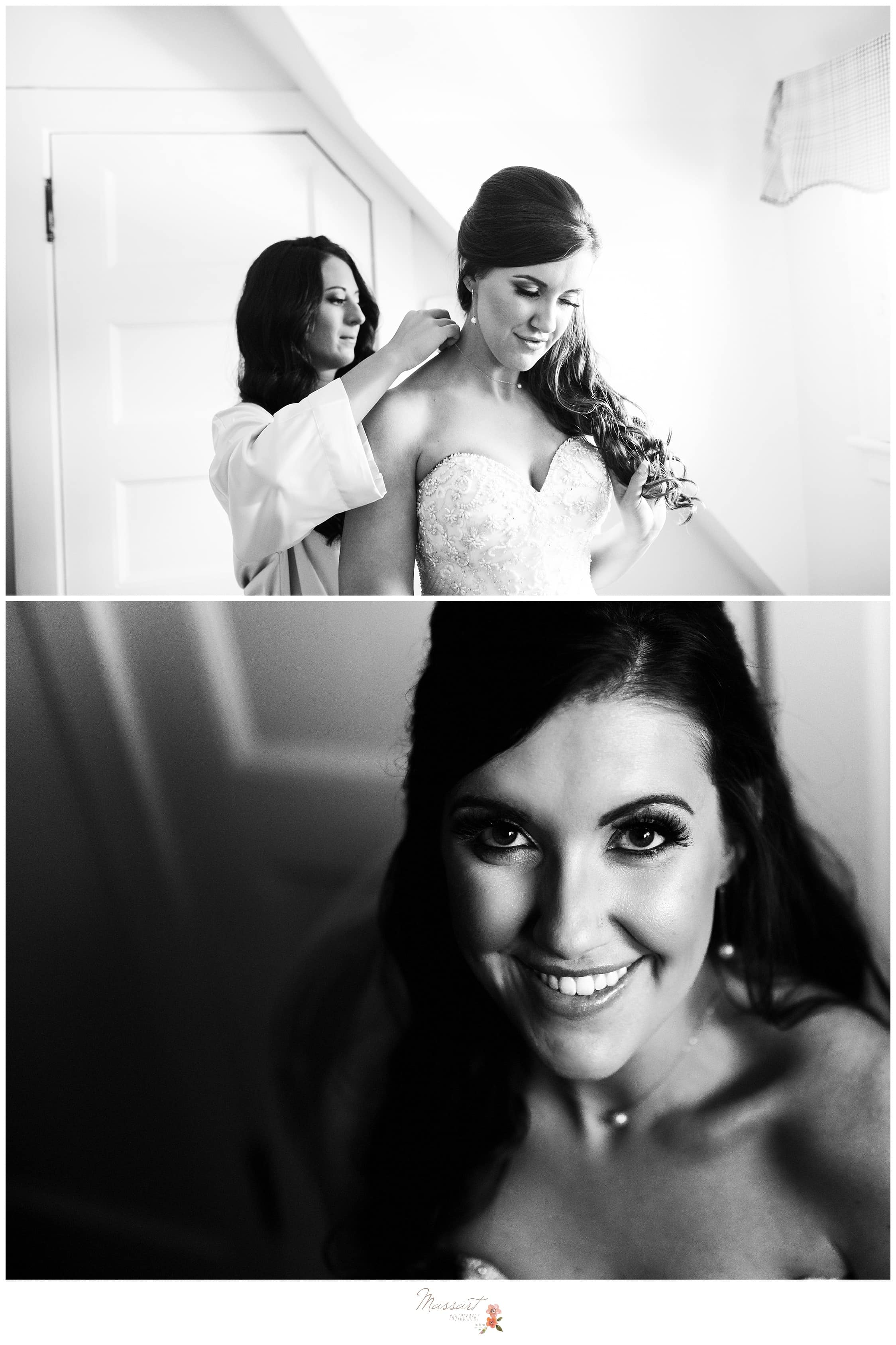 Bride smiles for a quick portrait as her maid of honor helps her tie on her necklace photographed by Massart Photography RI