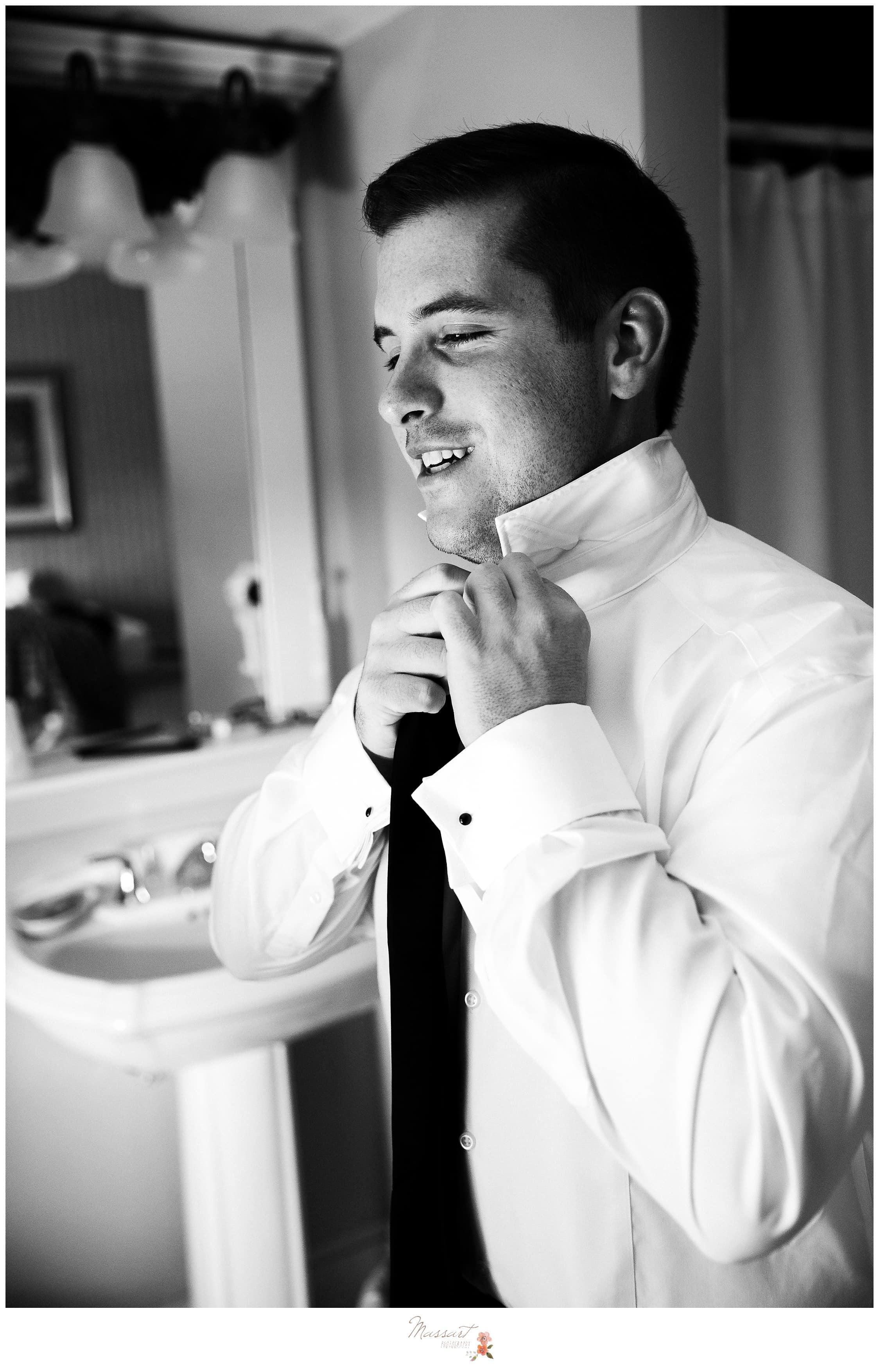 Groom puts on his tie in preparation for the wedding ceremony photographed by Massart Photography RI