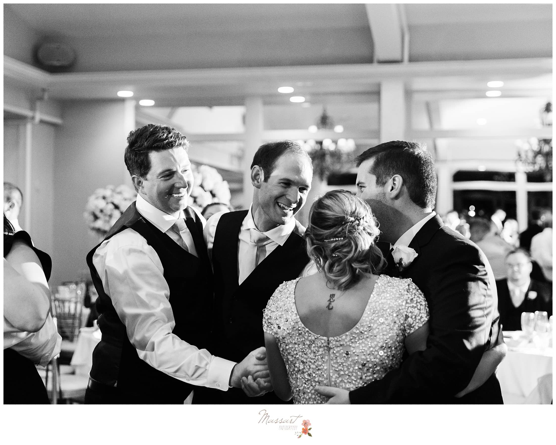 Bridesmaids and groomsmen dance along with the bride and groom photographed by Massart Photography Rhode Island