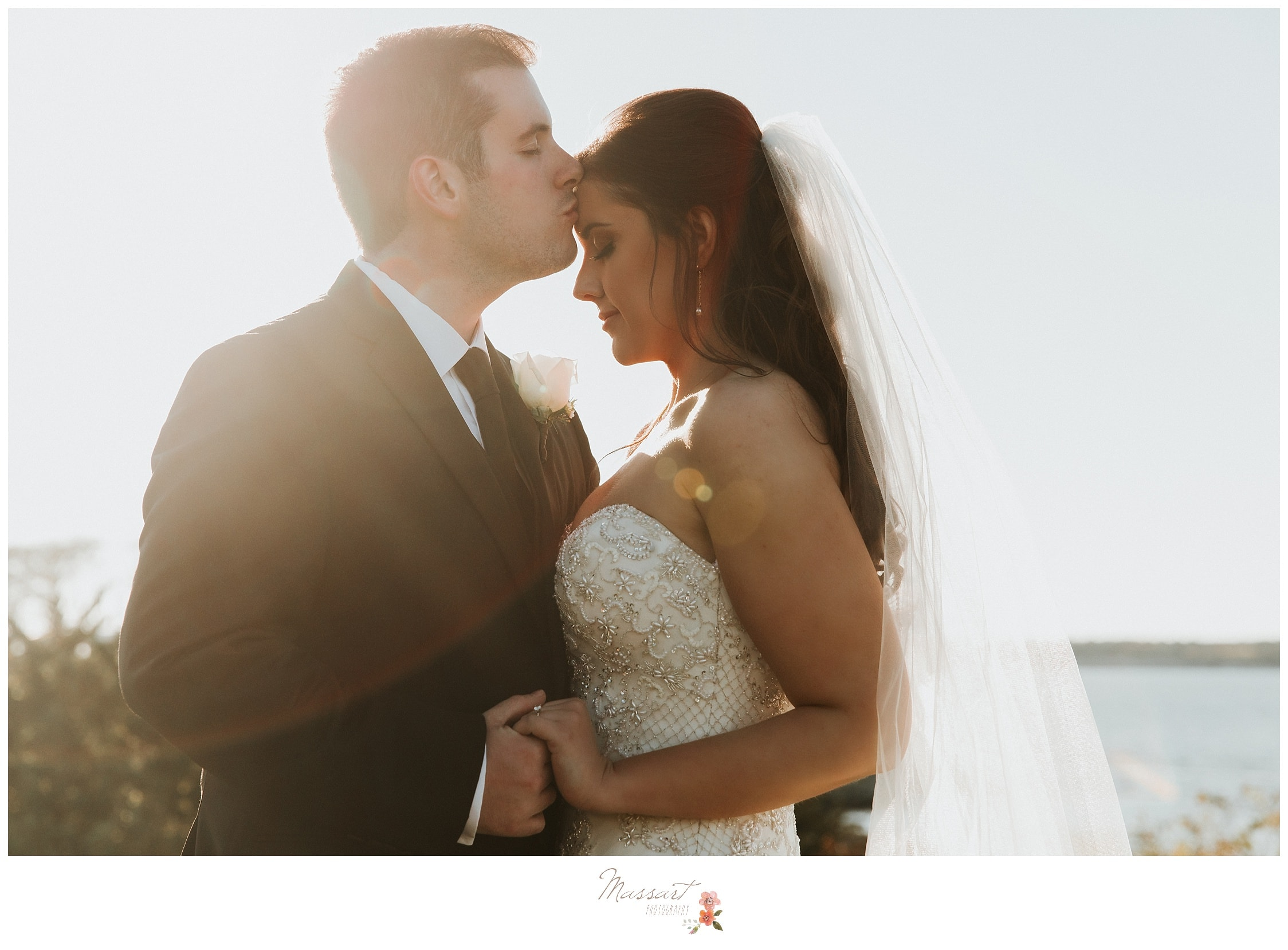 Groom kisses his bride with the sunlight in the background photographed by Massart Photography RI