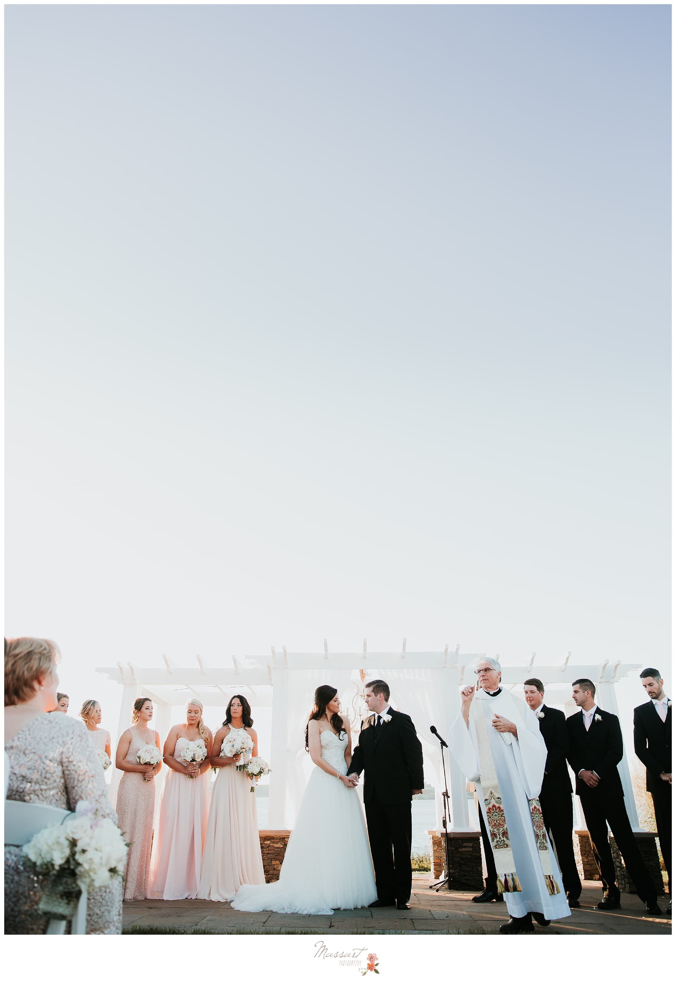 Ceremony under trellis at Ocean Cliff overlooking the water photographed by Massart Photography RI