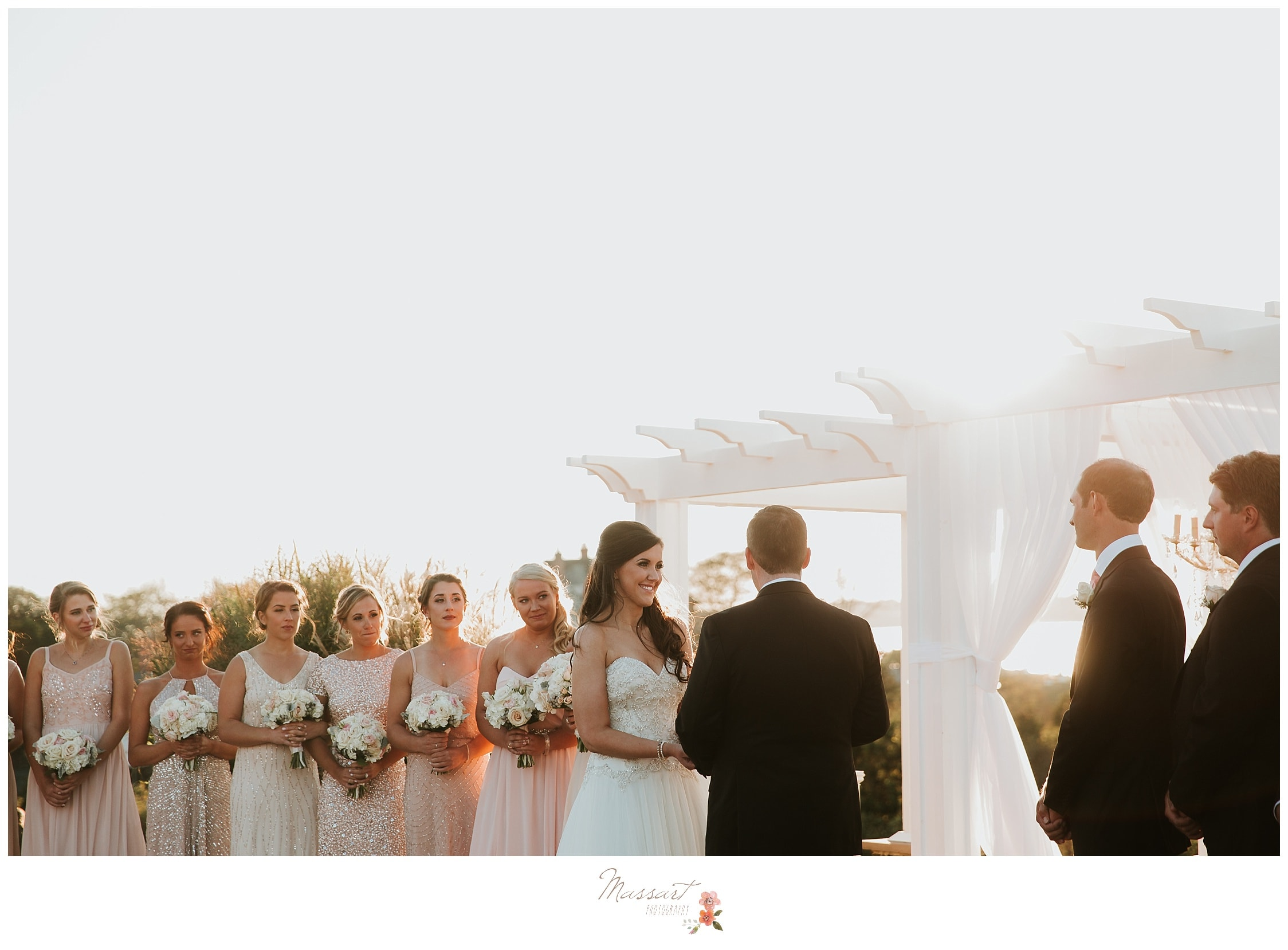 Wedding ceremony takes place under the trellis at Ocean Cliff Resort photographed by Massart Photography RI