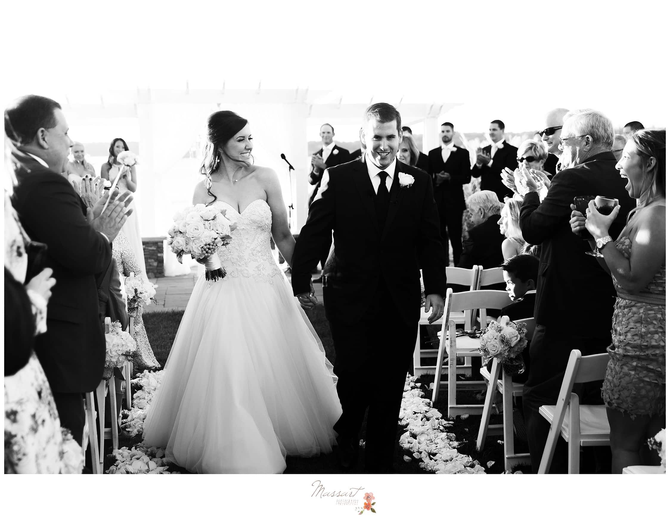 Black and white portrait of the bride and groom walking down the aisle photographed by Massart Photography RI