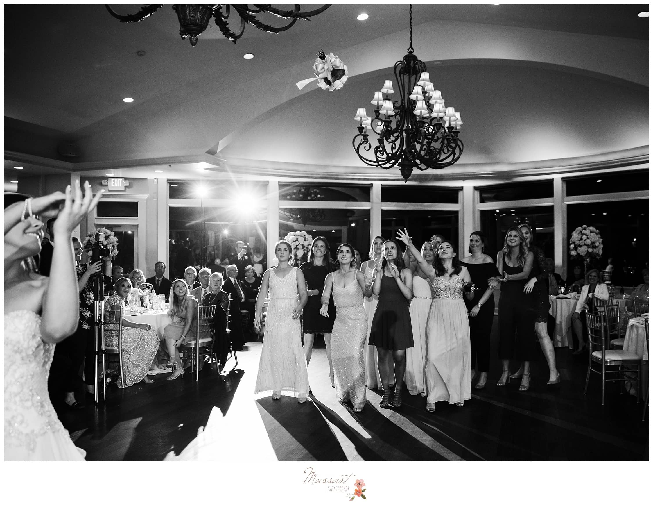 Bride throws bouquet at reception photographed by Massart Photography RI