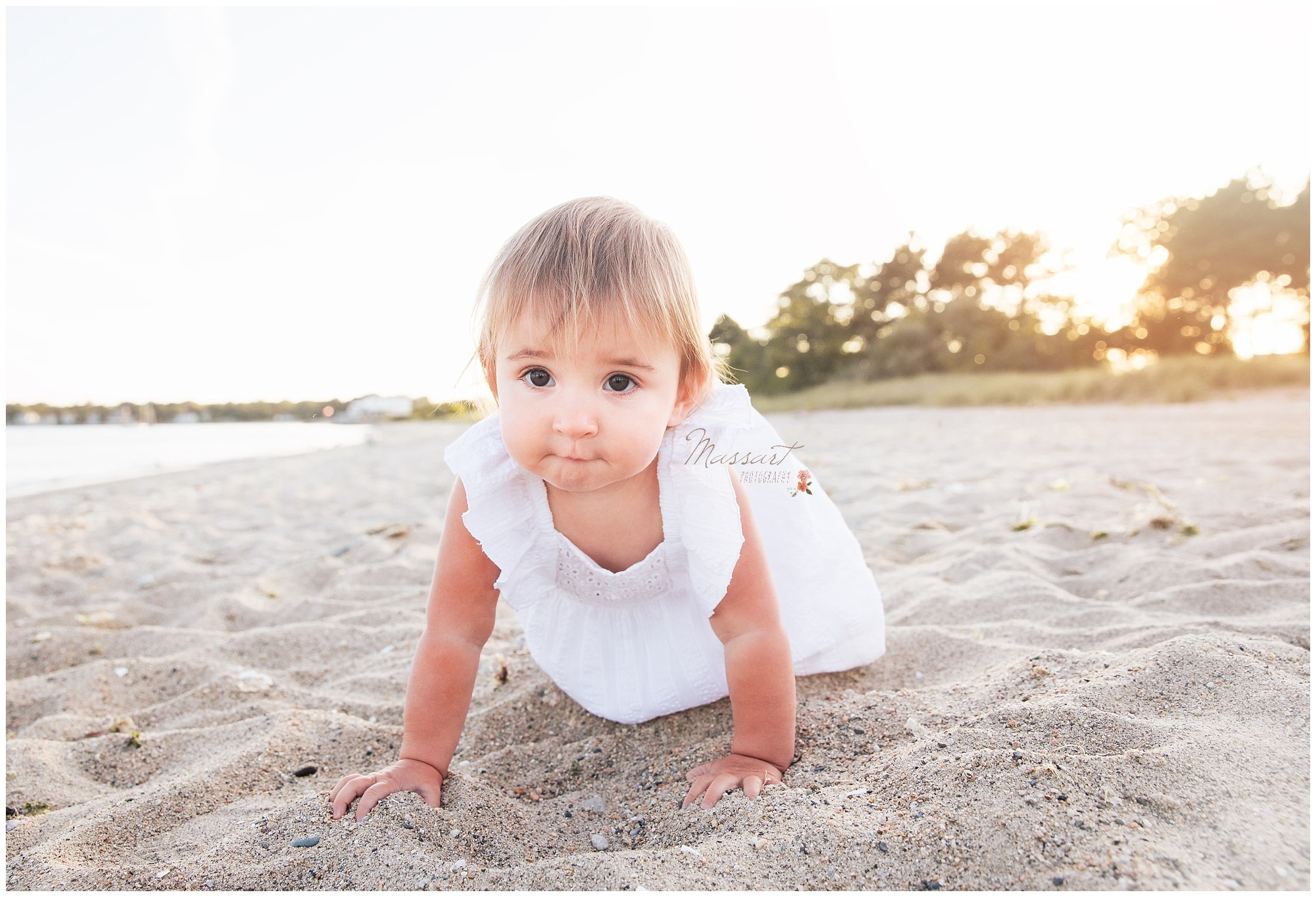 Little girl crawls in the sand during the family's portrait session photographed by Massart Photography RI