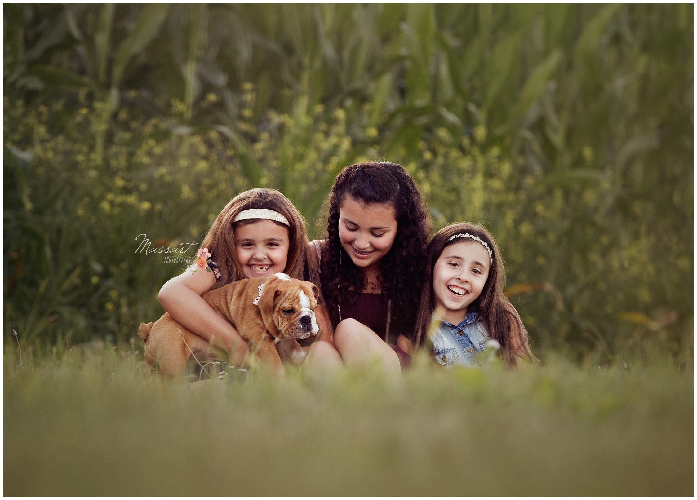 Siblings with their new dog outdoors during family portrait session photographed by Massart Photography RI