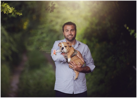 Dad holds new puppy under the trees during the family portrait session captured by Massart Photography Rhode Island