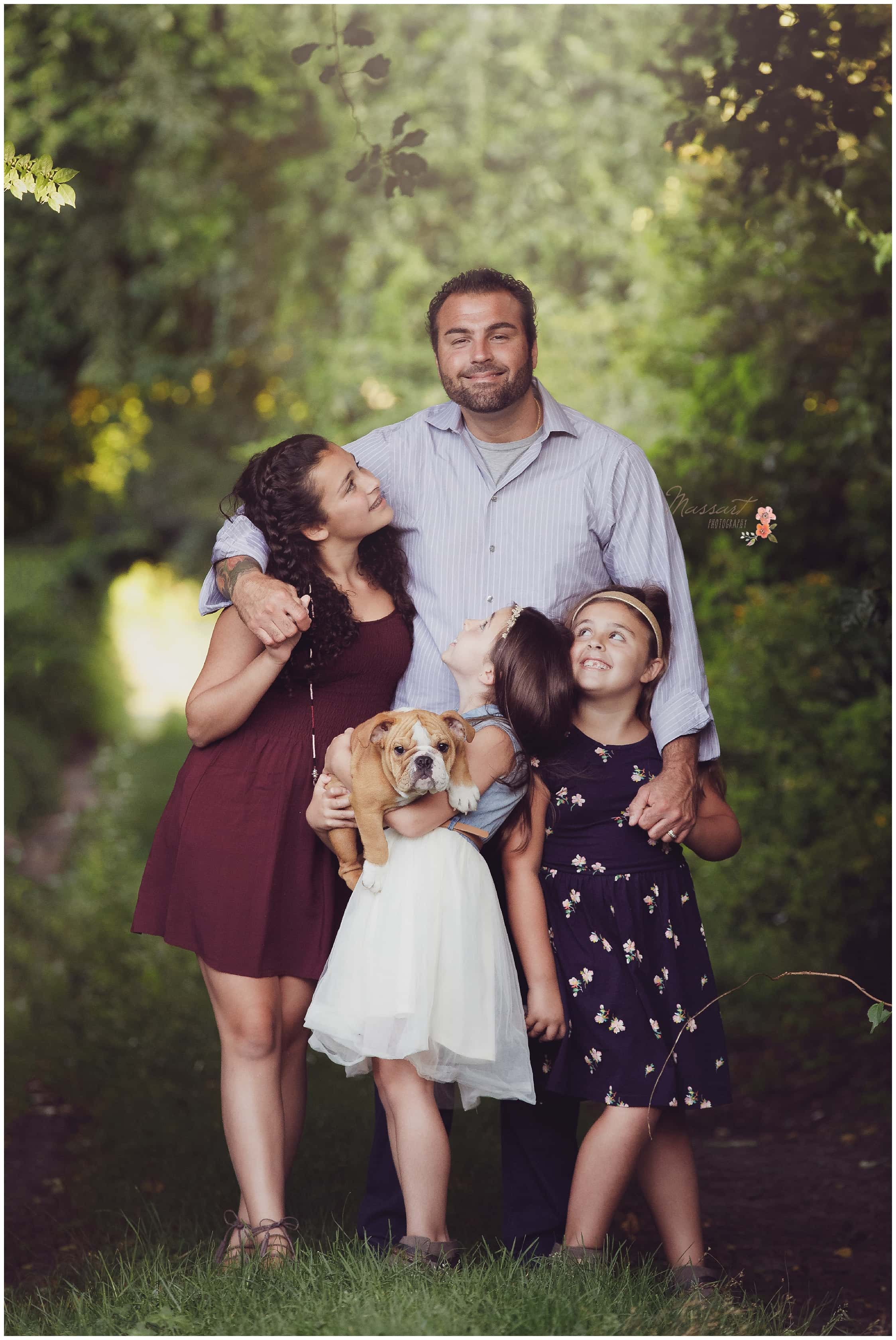 Dad and his daughters stand together under the trees during their family portrait session photographed by Massart Photography Rhode Island
