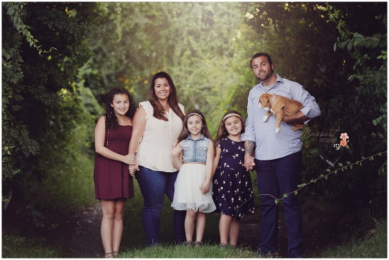 Family holds hand together with their new puppy during their outdoor family session under the trees captured by Massart Photography RI