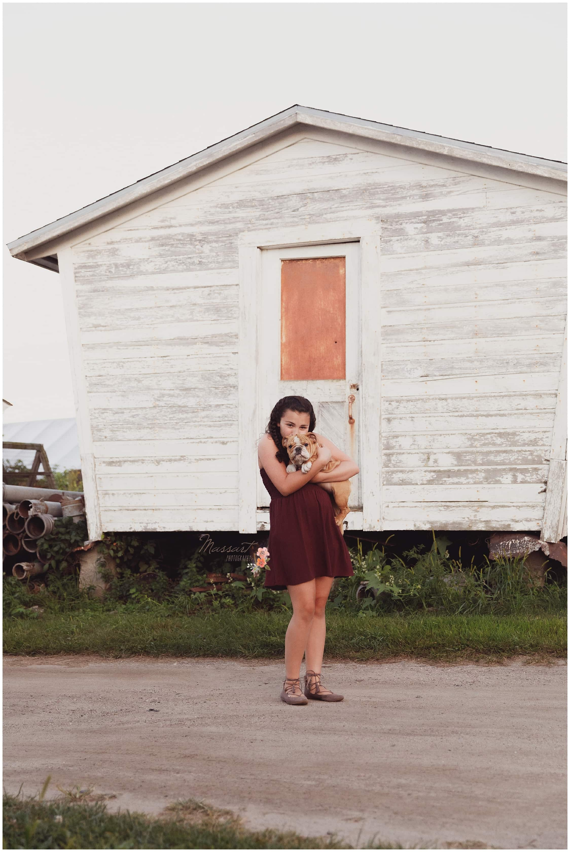 Teen girl stand outside rustic shed with her new puppy photographed by Massart Photography RI