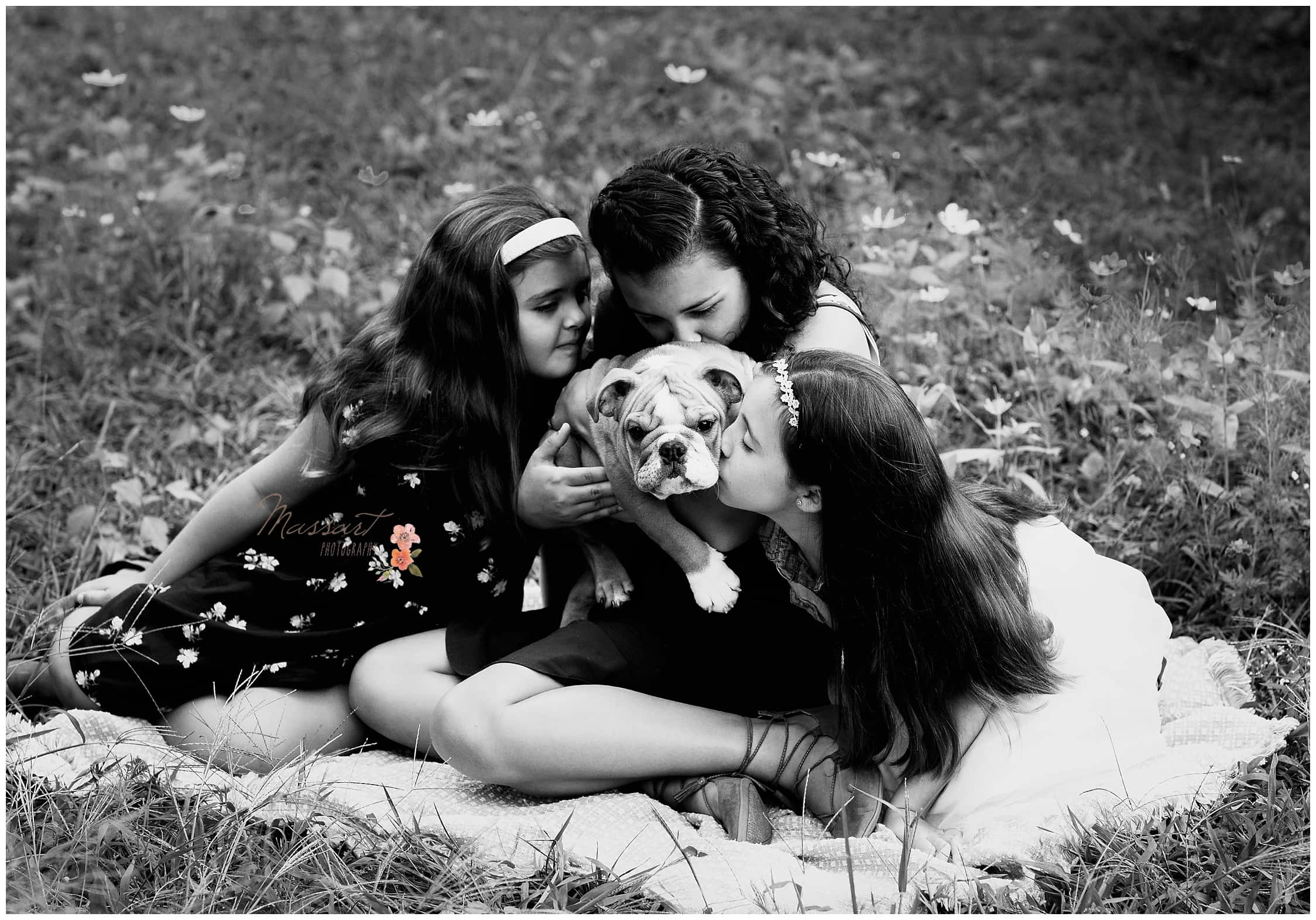 Sisters kiss their puppy during their outdoor family portrait session captured by Massart Photography of Warwick, Rhode Island