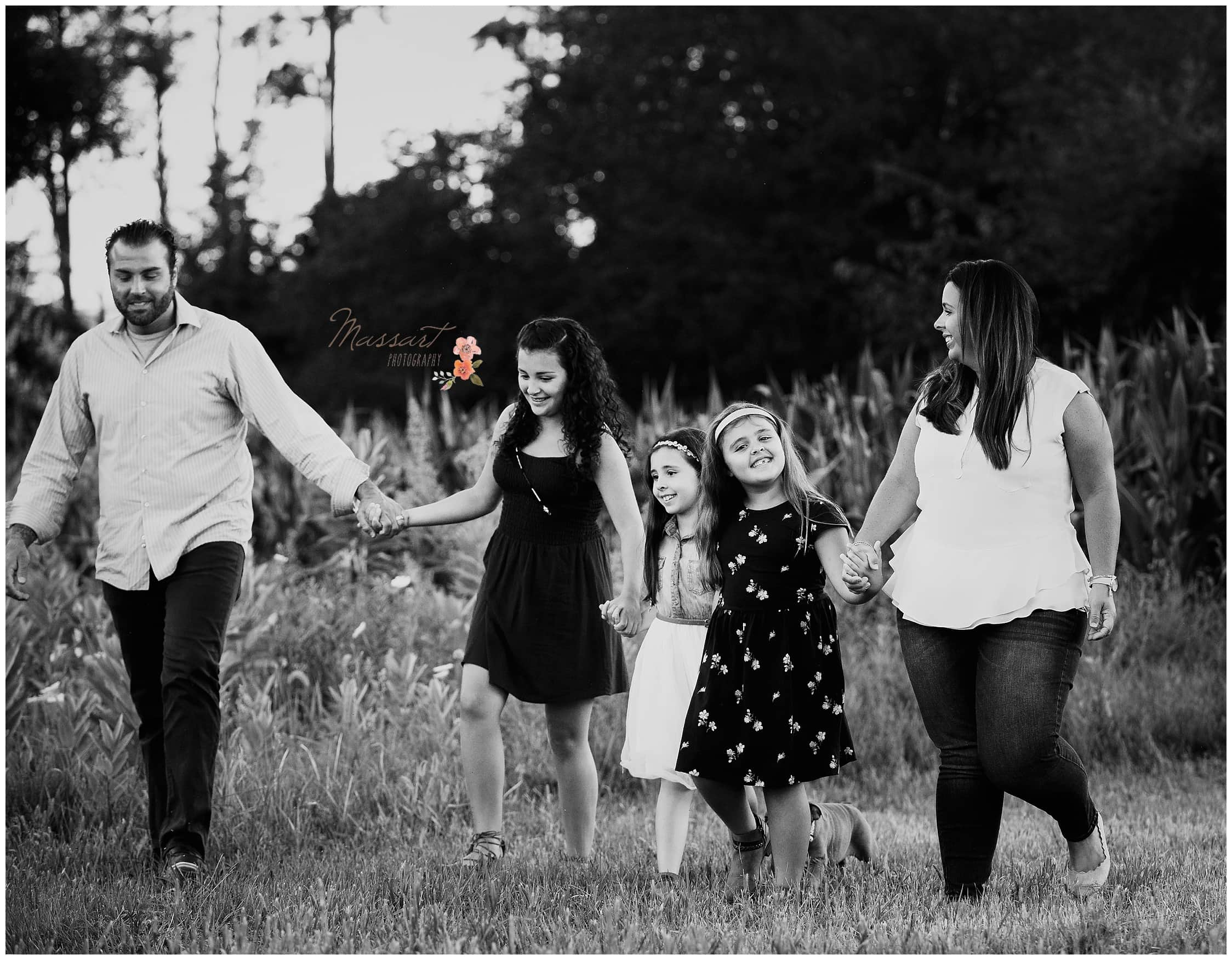 Black and white portrait of the family walking in the grass during their outdoor family portrait session captured by Massart Photography of Warwick, Rhode Island
