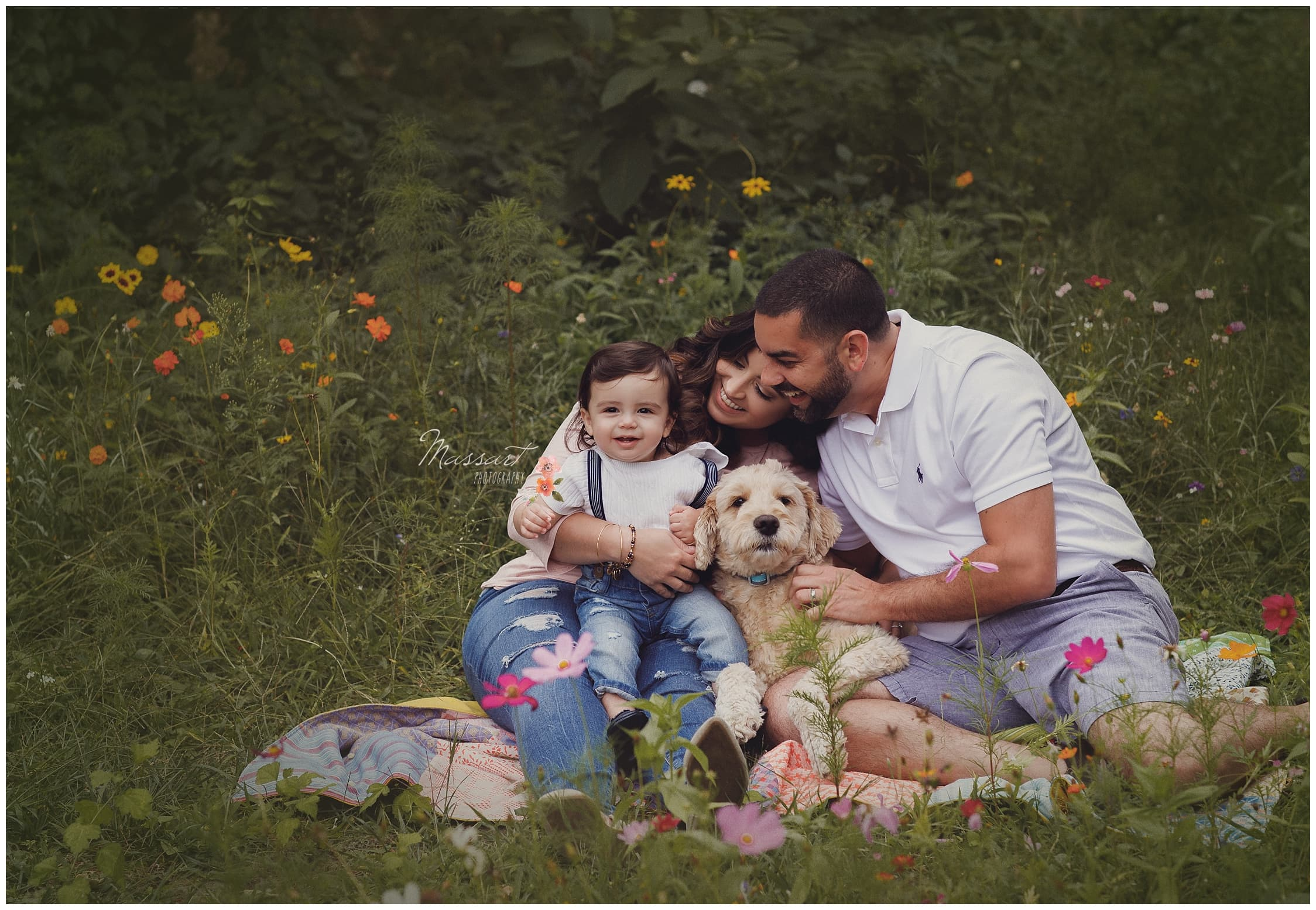Family sits outside in the grass with their dog photographed by Massart Photography Rhode Island
