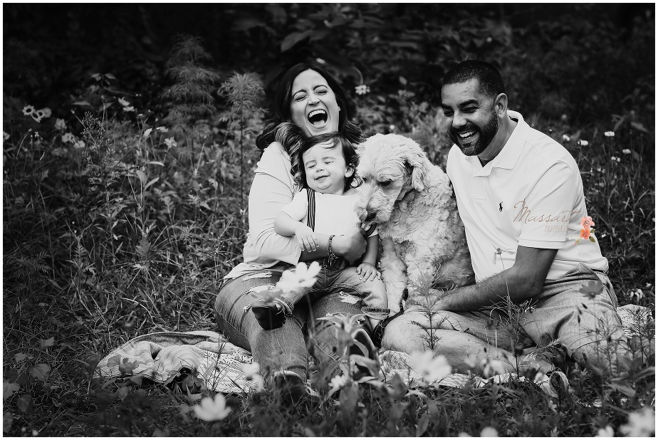Black and white portrait of the family and their dog having fun in the grass outdoors during son