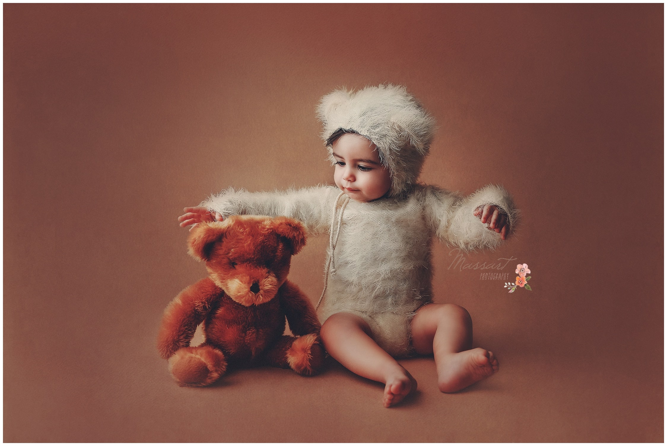 Little boy dressed in teddy bear onesie plays with his stuffed bear during his first year milestone session photographed by Massart Photography RI