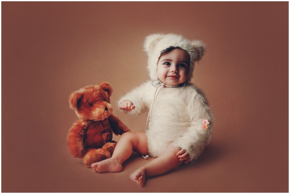 One year old boy laughs during his first birthday portrait session dressed as a teddy bear photographed by Massart Photography of Warwick, RI