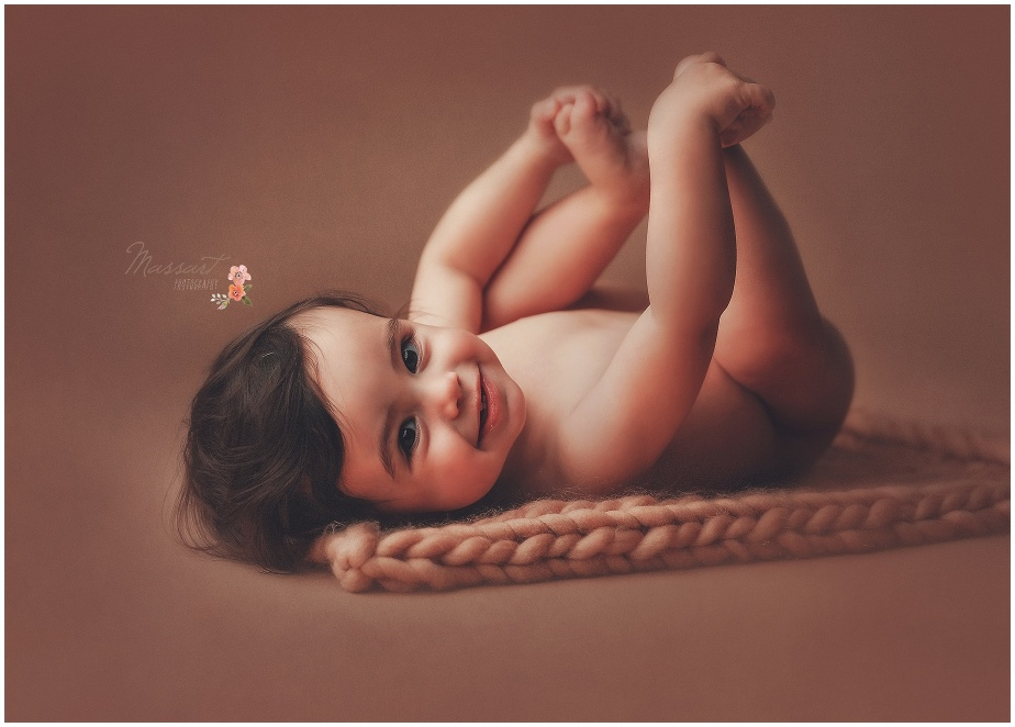 Baby holds his feet and laughs during his first birthday portrait session captured by Massart Photography Rhode Island
