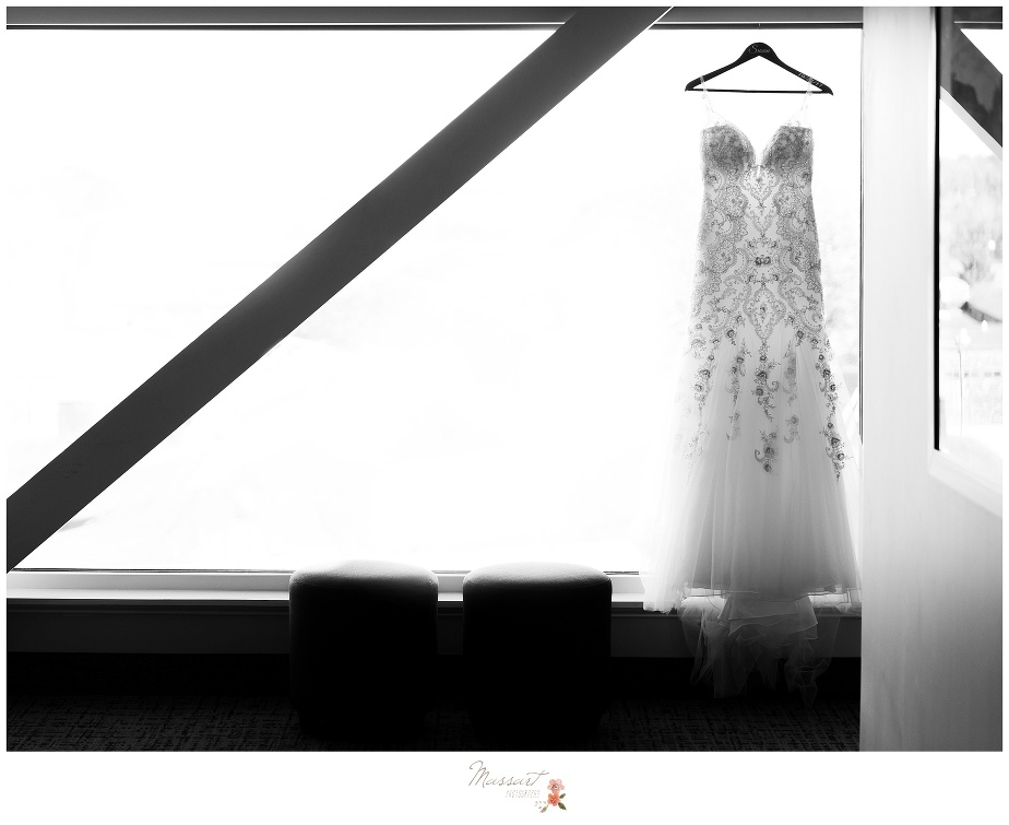 Black and white portrait of the bride's dress hanging in the window photographed by Massart Photography RI