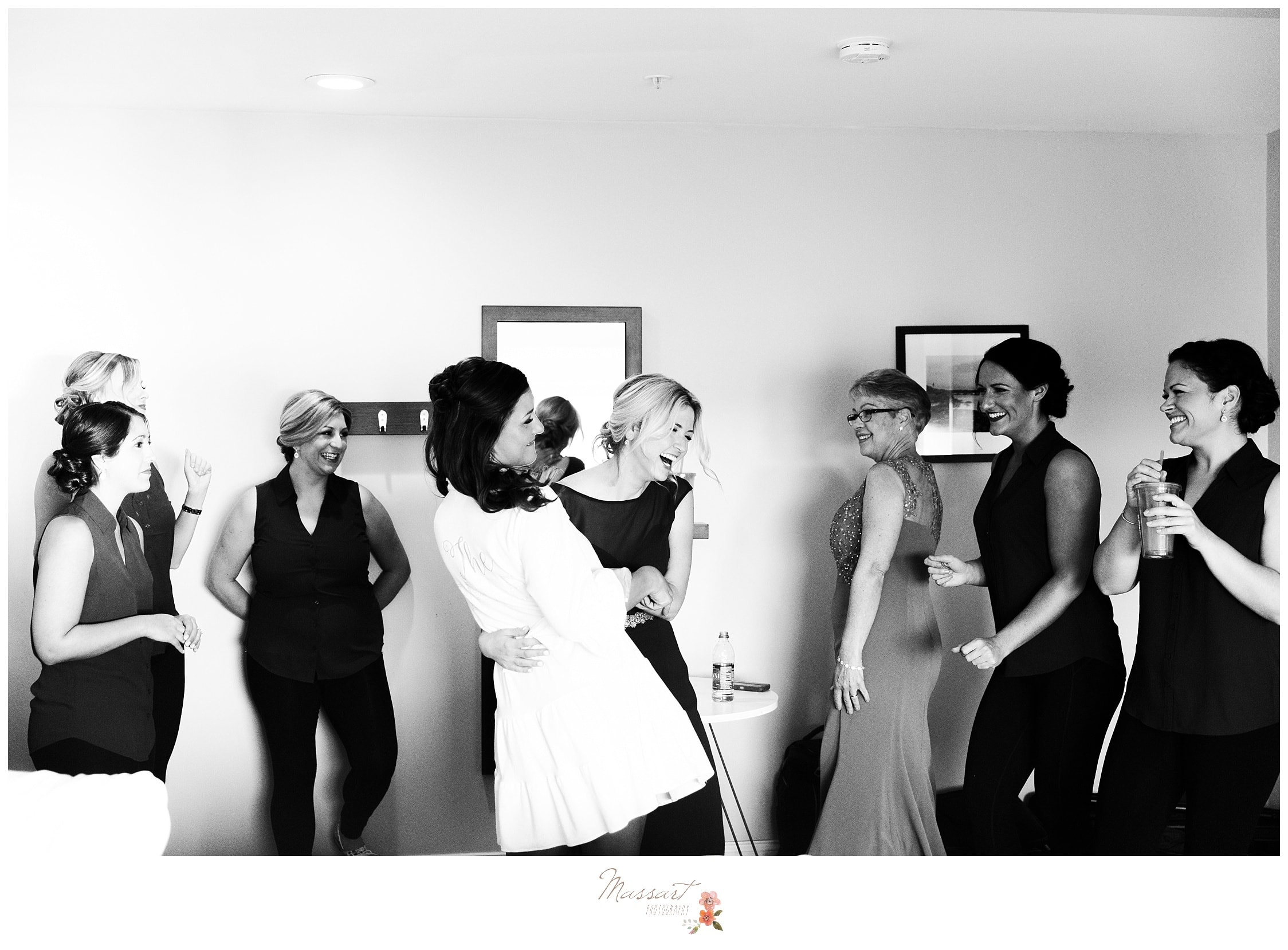 Bride, bridesmaids and her family have some fun while getting ready before the Atlantic Resort wedding photographed by Massart Photography RI