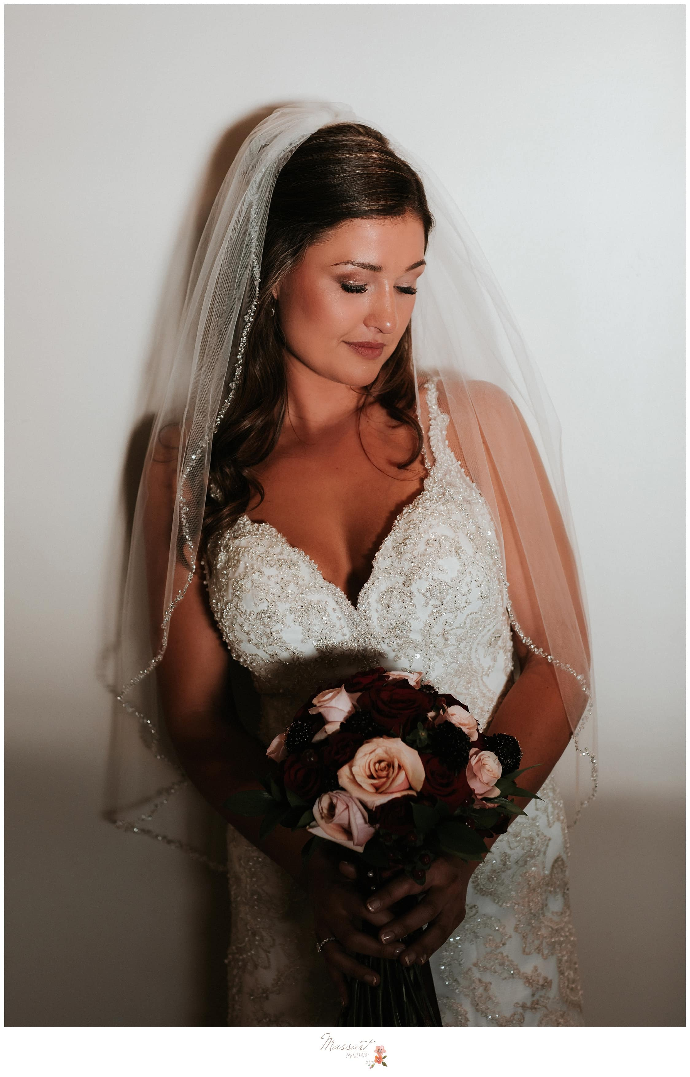 Bride poses in her wedding gown with her bouquet of flowers photographed by Massart Photography RI