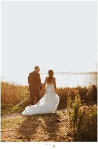Bride and groom walk hand in hand towards the water photographed by Massart Photography RI