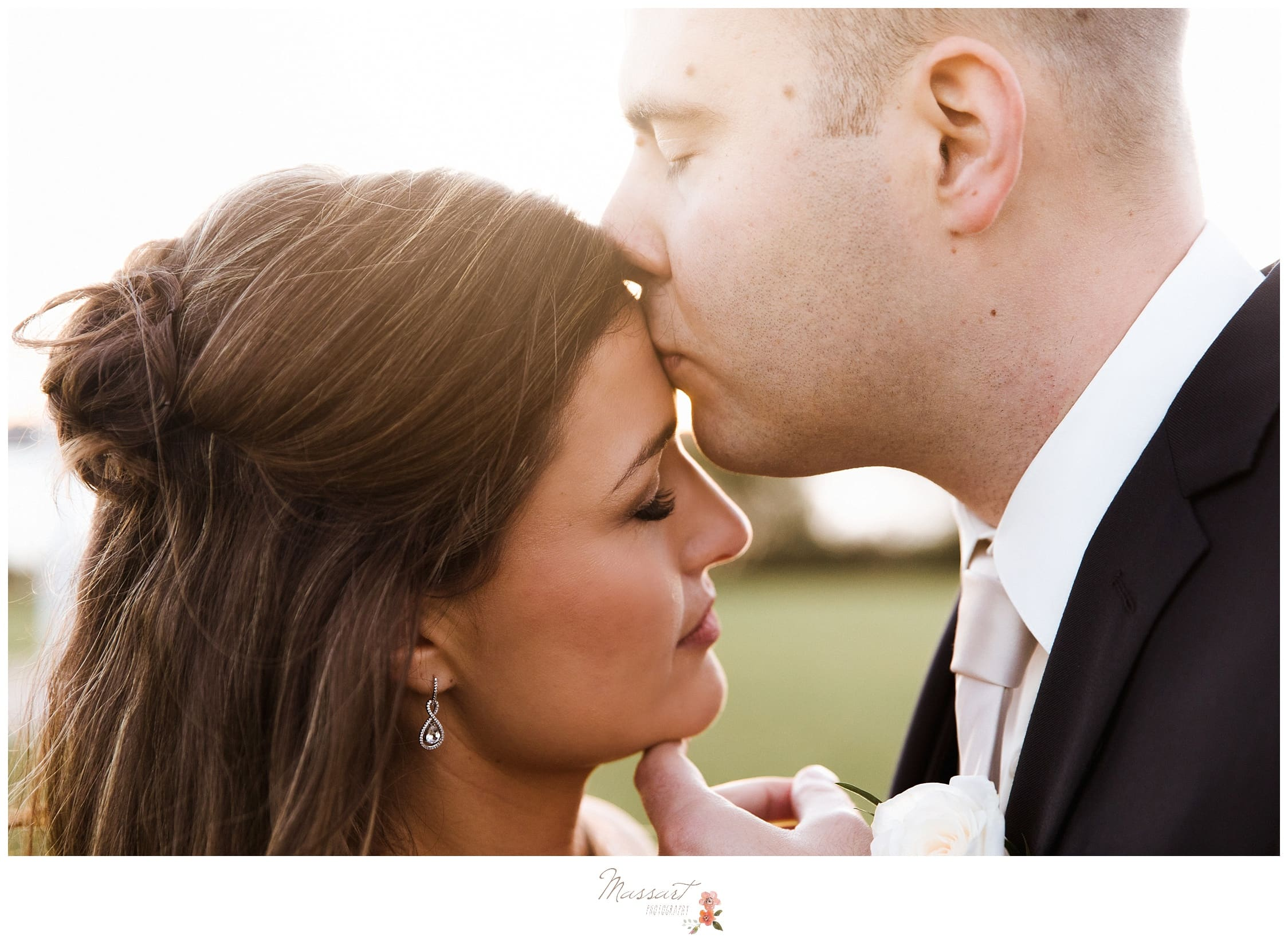 Groom kisses his bride outside their wedding venue photographed by Massart Photography Rhode Island
