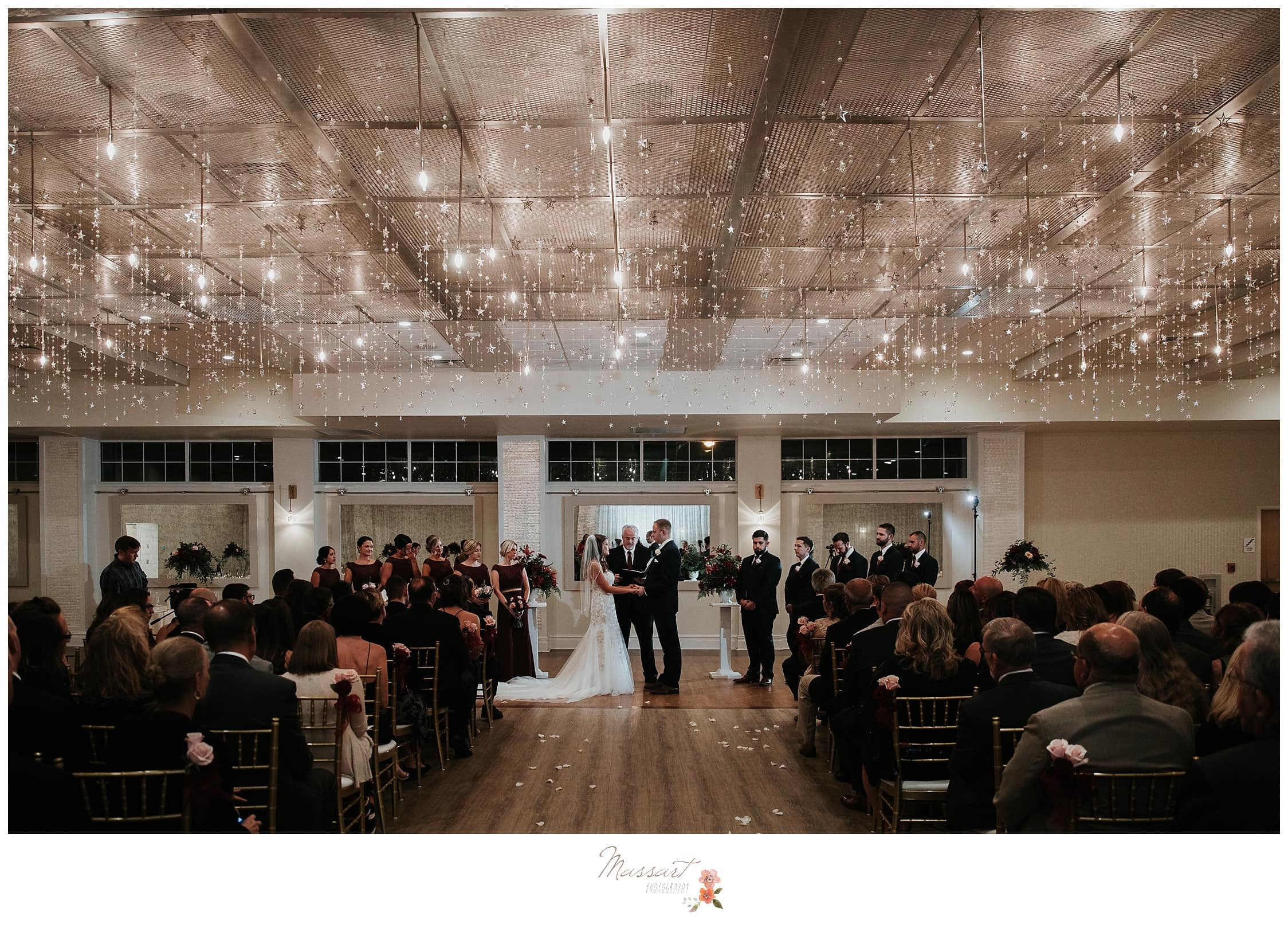 Romantic overview of the ceremony room as the bride and groom say their vows photographed by Massart Photography RI