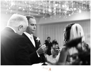 Black and white portrait of the groom sliding his wife's ring on her finger captured by Massart Photography RI