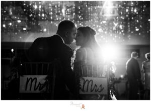 """Black and white portrait of the bride and groom at their table with chairs that say """"Mr. and Mrs."""" photographed by Massart Photography RI"""