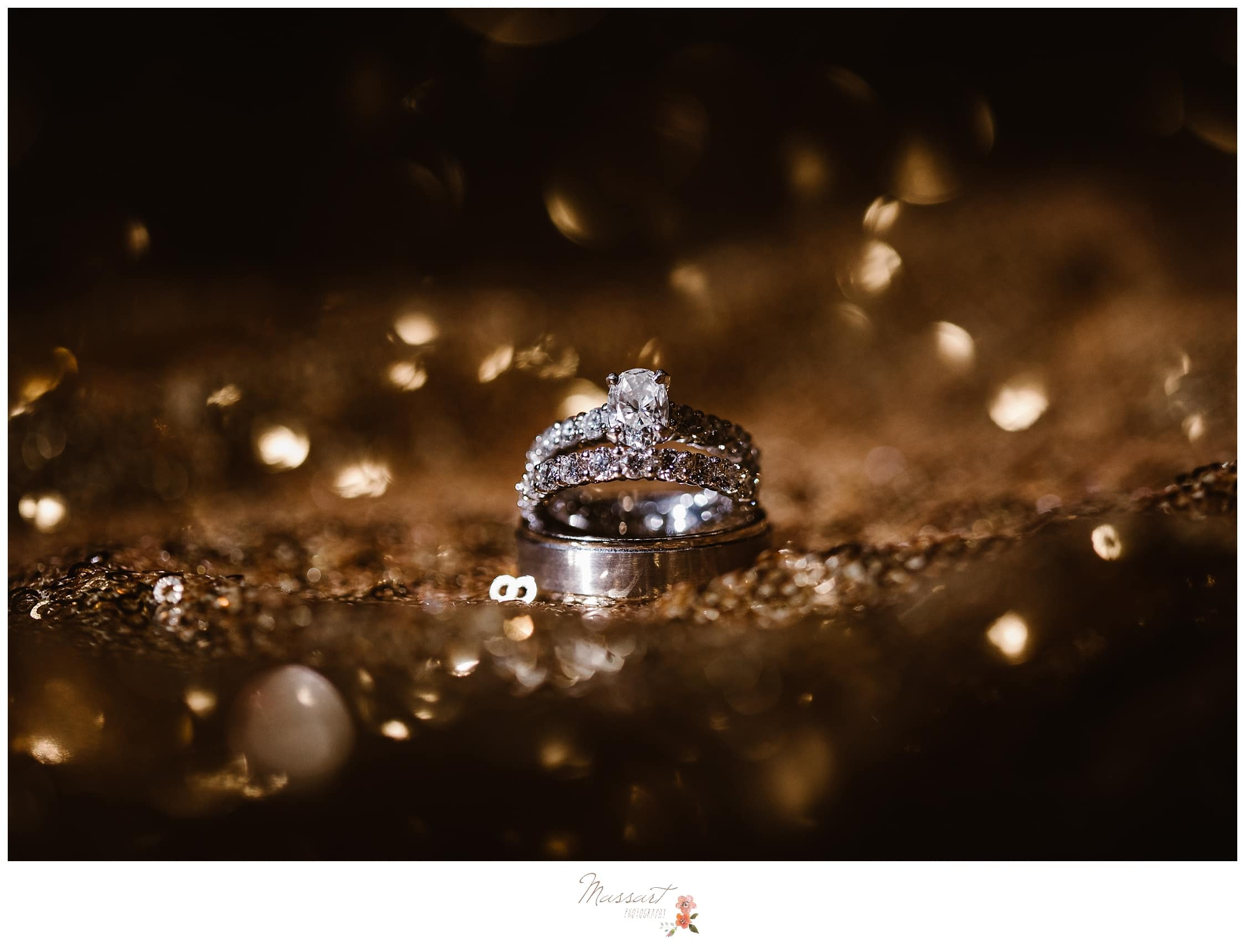 Portrait of the bride and groom's wedding ring on a glittery table cloth photographed by Massart Photography Rhode Island
